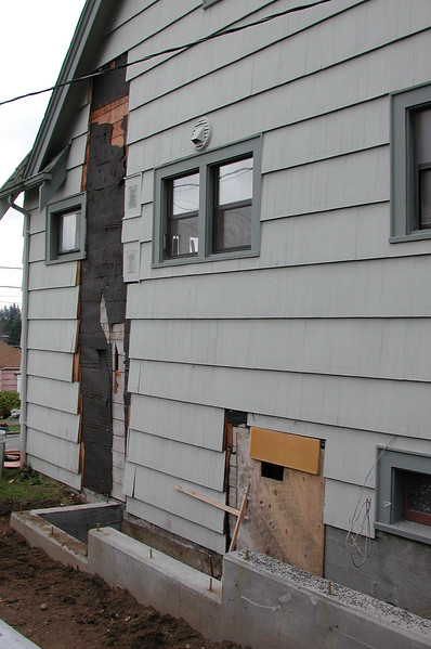 The addition will attach to the area with the siding stripped away. The original basement door, in the foreground, has been covered over.