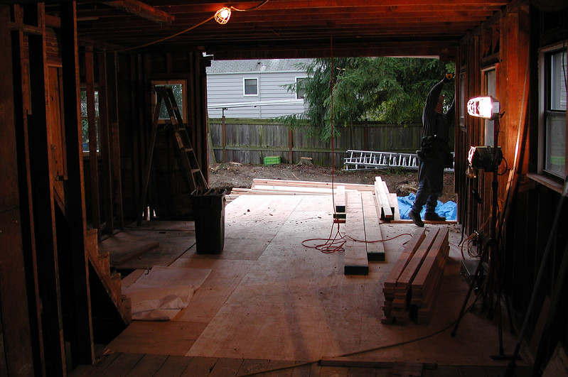 Downstairs with most of the walls missing. The addition has been framed up to the first floor.