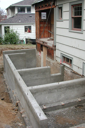 The finished foundation. The first section is where the stairs will be; behind that will be the porch (with a crawlspace); then the main part of the addition (with basement); and finally the basement stairs.