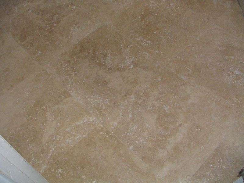 A close-up of the cream travertine tile floor after they added the grout.