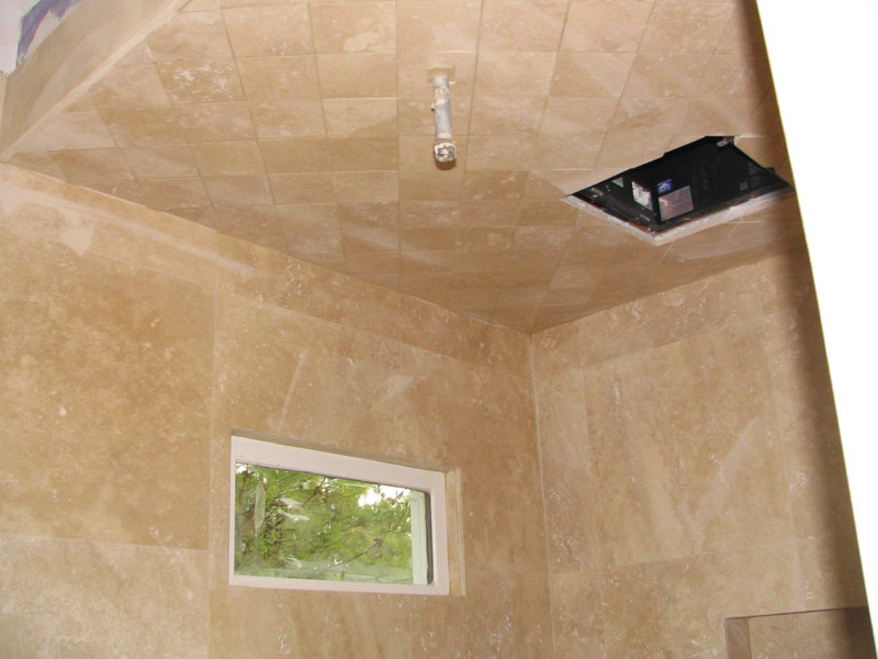 """This is the shower ceiling with grout.  They cut the shower floor and ceiling pieces from the same travertine tile.  They are 4"""" x 4"""" pieces.  They also replaced the ugly black window with this new transom window."""