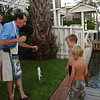 Papa Skip, helping the boys catch a fish off the backyard dock.