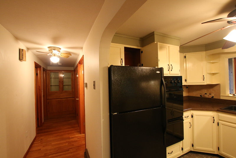 Kitchen and hallway leading to bathroom and rooms.