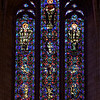 "Saint Vincent Ferrer Saint Raymond of Penafort Stained Glass Window by Charles Connick <br><br> <a href=""http://www.csvf.org/Architecture-N.html"">The church website</a> provides substantial panel-by-panel detail on the windows in the church. This beautiful window caught my eye, the Raymond of Penafort window. At the top center is Saint Raymond of Penafort. From the church website: ""St. Raymond of Penafort (1175-1275) holds his traditional symbols – a key and book. The key represents St. Raymond's priestly power to judge and absolve sin, which he exercised in a particular way as Pope Gregory IX's confessor and Grand Penitentiary. The books represents St. Raymond's own work, the Decretals, in which he collected and codified in one place the disparate canons and laws of the Church. The Decretals remains one of the most influential works of canon law in the history of the Church."" <br><br> The figure at the top right is St. Jean-Baptiste Marie Vianney, known popularly as the 'Curé d'Ars'. He  stands wearing the dark purple stole of the confessional with a penitent at his feet.  <br><br> At the top left is Saint Peter Nolasco. ""St. Peter Nolasco (1189-1256) was tutor to the Royal Court of Peter of Aragon. Because of his concern for Christians enslaved by the Moors, he devoted his life to the freeing the Christians and converting the Moors. St. Raymond of Penafort was also interested in this work of evangelization. St. Peter is portrayed here with the habit of the Mercedarians, the Order he founded. The badge of the Order can be seen on his chest. Around his neck are the broken chains of a ransomed Christian. A freed captive is kneeling at his feet."" <br><br> See the church website for much more detail. <br><br> Charles Connick (1875–1945) was a prominent artist best known for his work in stained glass in the Gothic Revival style. He was born in Crawford Country, Pennsylvania and developed an interest in drawing at an early age. He left high school when his father became disabled to become an illustrator on the staff of the Pittsburgh Press. At the age of 19, he learned the art of stained glass as an apprentice in the shop of Rudy Brothers in Pittsburgh, where he stayed through 1899. He worked for a number of stained glass companies in Pittsburgh and New York. He went to England and France to study ancient and modern stained glass, including those in the Chartres Cathedral. His first major work was First Baptist Church in Pittsburgh in 1912. Connick settled in Boston opening a stained glass studio in Back Bay in 1913; the Charles J. Connick Associates Studio continued to operate after his death until 1986. He produced many notable windows in such churches as Saint Patrick's Cathedral, Saint John the Divine, the Princeton University Chapel, and Saint Vincent Ferrer. According to Wikipedia, the Charles J. Connick Associates Studio produced some 15,000 windows in more than 5,000 churches and public buildings. <br><br> According to <a href=""http://en.wikipedia.org/wiki/Charles_Connick"">Wikipedia, </a> ""Connick preferred to use clear ""antique"" glass, similar to that of the Middle Ages and praised this type of glass as ""colored radiance, with the lustre, intensity, and baffling vibrant quality of dancing lights."" He employed a technique of ""staggered"" solder-joints in his leading and bars, which English stained-glass historian Peter Cormack says gives the windows their ""syncopated or 'swinging' character."" His style incorporated a strong interest in symbolism as well. Connick expressed the opinion that stained glass's first job was to serve the architectural effect and he believed that his greatest contribution to glasswork was ""rescuing it from the abysmal depth of opalescent picture windows"" of the sort popularized by Louis Comfort Tiffany and John La Farge. Although firmly committed to a regenerated handicraft tradition, Connick welcomed innovation and experimentation in design and technique among his co-workers at his studio."" <br><br> According to the <a href=""http://www.cjconnick.org/"">Charles J. Connick Stained Glass Foundation website</a> ""Using pure, intense color and strong linear design, this guild of artists led the modern revitalization of medieval stained glass craftsmanship in the United States.  Their work reflected a strong interest in symbolism in design and color, and stressed the importance of the relationship between the window's design and its surrounding architecture.  As if with one mind and one pair of hands, the craftsmen in the Connick Studio worked collectively on their windows like the 12th- and 13th- century artisans whose craft inspired them."" <br><br> The Charles J. Connick Stained Glass Foundation was formed after the studio closed in 1986. According to the <a href=""http://www.cjconnick.org/"">foundation website</a> ""The mission of the Charles J. Connick Stained Glass Foundation, Ltd. is to promote the true understanding of the glorious medium of color and light and to preserve and perpetuate the Connick tradition of stained glass."" <br><br> Here is an interesting <a href=""http://video.mit.edu/watch/charles-j-connick-and-mit-10153/"">video from the Massachusetts Institute of Technology</a> on Connick. In December 2008, the foundation donated materials to the MIT's Rotch Library of Architecture and Planning to form the Charles J. Connick Stained Glass Foundation Collection."