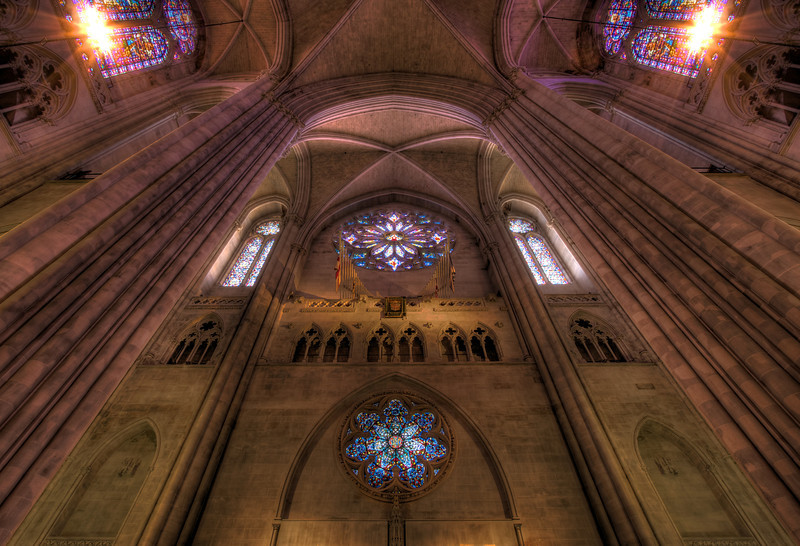 "Cathedral of Saint John the Divine Rose Window by Charles Connick <br><br> This is the West Rose window above the front entrance. According to information from the church, Charles Connick designed the Great Rose Window at the top in 1933. It depicts Christ in Glory, surrounded by angels, beatitudes, the four evangelists (Matthew, Mark, Luke, John), the prophets (Isaiah, Jeremiah, Daniel, and Ezekiel), Divine Love, Seraphim, and Divine Wisdom: Cherubim. <br><br> The Lower Rose window is also by Connick in 1933. ""The seven points of the star are derived from the Revelation of St. John. In the center is Our Lords Monogram, IHS, the first three letters of Jesus in Greek, surrounded by seven fountains, seven vines, seven pairs of doves and seven stars."" <br><br> Charles Connick (1875–1945) was a prominent artist best known for his work in stained glass in the Gothic Revival style. He was born in Crawford Country, Pennsylvania and developed an interest in drawing at an early age. He left high school when his father became disabled to become an illustrator on the staff of the Pittsburgh Press. At the age of 19, he learned the art of stained glass as an apprentice in the shop of Rudy Brothers in Pittsburgh, where he stayed through 1899. He worked for a number of stained glass companies in Pittsburgh and New York. He went to England and France to study ancient and modern stained glass, including those in the Chartres Cathedral. His first major work was First Baptist Church in Pittsburgh in 1912. Connick settled in Boston opening a stained glass studio in Back Bay in 1913; the Charles J. Connick Associates Studio continued to operate after his death until 1986. He produced many notable windows in such churches as Saint Patrick's Cathedral, Saint John the Divine, the Princeton University Chapel, and Saint Vincent Ferrer. According to Wikipedia, the Charles J. Connick Associates Studio produced some 15,000 windows in more than 5,000 churches and public buildings. <br><br> According to <a href=""http://en.wikipedia.org/wiki/Charles_Connick"">Wikipedia, </a> ""Connick preferred to use clear ""antique"" glass, similar to that of the Middle Ages and praised this type of glass as ""colored radiance, with the lustre, intensity, and baffling vibrant quality of dancing lights."" He employed a technique of ""staggered"" solder-joints in his leading and bars, which English stained-glass historian Peter Cormack says gives the windows their ""syncopated or 'swinging' character."" His style incorporated a strong interest in symbolism as well. Connick expressed the opinion that stained glass's first job was to serve the architectural effect and he believed that his greatest contribution to glasswork was ""rescuing it from the abysmal depth of opalescent picture windows"" of the sort popularized by Louis Comfort Tiffany and John La Farge. Although firmly committed to a regenerated handicraft tradition, Connick welcomed innovation and experimentation in design and technique among his co-workers at his studio."" <br><br> According to the <a href=""http://www.cjconnick.org/"">Charles J. Connick Stained Glass Foundation website</a> ""Using pure, intense color and strong linear design, this guild of artists led the modern revitalization of medieval stained glass craftsmanship in the United States.  Their work reflected a strong interest in symbolism in design and color, and stressed the importance of the relationship between the window's design and its surrounding architecture.  As if with one mind and one pair of hands, the craftsmen in the Connick Studio worked collectively on their windows like the 12th- and 13th- century artisans whose craft inspired them."" <br><br> The Charles J. Connick Stained Glass Foundation was formed after the studio closed in 1986. According to the <a href=""http://www.cjconnick.org/"">foundation website</a> ""The mission of the Charles J. Connick Stained Glass Foundation, Ltd. is to promote the true understanding of the glorious medium of color and light and to preserve and perpetuate the Connick tradition of stained glass."" <br><br> Here is an interesting <a href=""http://video.mit.edu/watch/charles-j-connick-and-mit-10153/"">video from the Massachusetts Institute of Technology</a> on Connick. In December 2008, the foundation donated materials to the MIT's Rotch Library of Architecture and Planning to form the Charles J. Connick Stained Glass Foundation Collection. <br><br> This shot is captured with a focal length of 16mm. This is an HDR combining three exposures (-2, 0, 2) ranging in duration from 2 seconds to 30 seconds at f8, 100 ISO."