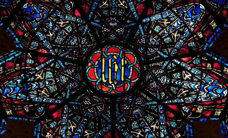 """Saint John the Divine Lesser Rose Window by Charles Connick (1933) <br><br> According to material from the church, Charles Connick designed the Great Rose Window in 1933. """"The seven points of the star are derived from the Revelation of St. John. Int the center is Our Lords Monogram, IHS, the first three letters of Jesus in Greek, surrounded by seven fountains, seven vines, seven pairs of doves, and seven stars."""" <br><br> This is one of the first photos I took with a long telephoto lens, a Canon 70-200 f4 USM. My work up to that point was with much wider angle lenses, 10-22mm or 17-55mm, which provides a nice overall view of a window. However, I wanted a much closer perspective, tight enough to see the artist's detail of the work. Considering the 1.6X crop factor, this was shot at 300mm.  <br><br> Charles Connick (1875–1945) was a prominent artist best known for his work in stained glass in the Gothic Revival style. He was born in Crawford Country, Pennsylvania and developed an interest in drawing at an early age. He left high school when his father became disabled to become an illustrator on the staff of the Pittsburgh Press. At the age of 19, he learned the art of stained glass as an apprentice in the shop of Rudy Brothers in Pittsburgh, where he stayed through 1899. He worked for a number of stained glass companies in Pittsburgh and New York. He went to England and France to study ancient and modern stained glass, including those in the Chartres Cathedral. His first major work was First Baptist Church in Pittsburgh in 1912. Connick settled in Boston opening a stained glass studio in Back Bay in 1913; the Charles J. Connick Associates Studio continued to operate after his death until 1986. He produced many notable windows in such churches as Saint Patrick's Cathedral, Saint John the Divine, the Princeton University Chapel, and Saint Vincent Ferrer. According to Wikipedia, the Charles J. Connick Associates Studio produced some 15,000 windows in more than 5,000 churc"""
