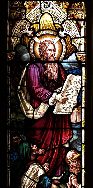 """The Church of the Incarnation, Moses and the Law by Heaton, Butler and Bayne <br><br> This is an Old Testament window, the lower portion  shows Moses giving the Law. <br><br> Clement Heaton originally founded his stained glass firm in 1852, joined by James Butler in 1855. Between 1859-61 they worked alongside Clayton and Bell and were joined by Robert Turnill Bayne, who became their sole designer and a full partner in the firm from 1862. His windows show strong design and color, and are often recognizable by the inclusion of at least one figure with Bayne's features and long beard to <a href=""""http://en.wikipedia.org/wiki/Heaton,_Butler_and_Bayne"""">Wikipedia.</a>. They established their studio in Covent Garden, London, and went on to become one of the leading firms of Gothic Revival stained glass manufacturers, whose work was commissioned by the principal Victorian architects. A change in direction came with their production of windows to the designs of Henry Holiday in 1868, which show a more classical influence at work. During a long career, the firm produced stained glass for numerous churches throughout the U.K. and the U.S. <br><br> During the Medieval period, from the Norman Conquest of England in 1066 until the 1530s, much stained glass was produced and installed in churches, monasteries and cathedrals. Two historic events had brought an end to this and the destruction of most of the glass-the Dissolution of the Monasteries under Henry VIII and the Puritan era under Oliver Cromwell in the 17th century. <br><br> The early 19th century was marked by a renewal of the Christian faith, a growth of Roman Catholicism, a planting of new churches, particularly in centers of industrial growth and the restoration of many ancient churches and cathedrals. In the 1850s a number of young designers worked in conjunction with the leading Gothic Revival architects in the provision of stained glass for new churches and for the restoration of old; the work of John Richard Clayton,"""