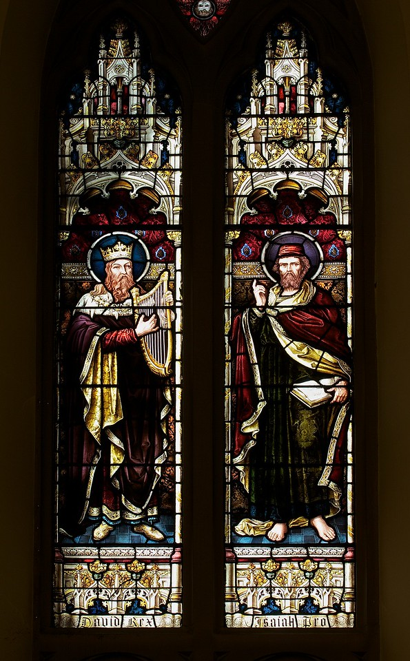 """The Church of the Incarnation, Moses and the Law by Heaton, Butler, and Bayne <br><br> This is an Old Testament window, the upper window depicts David and Isaiah, who represent the Psalms and the Prophets.  <br><br> Clement Heaton originally founded his stained glass firm in 1852, joined by James Butler in 1855. Between 1859-61 they worked alongside Clayton and Bell and were joined by Robert Turnill Bayne, who became their sole designer and a full partner in the firm from 1862. His windows show strong design and color, and are often recognizable by the inclusion of at least one figure with Bayne's features and long beard to <a href=""""http://en.wikipedia.org/wiki/Heaton,_Butler_and_Bayne"""">Wikipedia.</a>. They established their studio in Covent Garden, London, and went on to become one of the leading firms of Gothic Revival stained glass manufacturers, whose work was commissioned by the principal Victorian architects. A change in direction came with their production of windows to the designs of Henry Holiday in 1868, which show a more classical influence at work. During a long career, the firm produced stained glass for numerous churches throughout the U.K. and the U.S. <br><br> During the Medieval period, from the Norman Conquest of England in 1066 until the 1530s, much stained glass was produced and installed in churches, monasteries and cathedrals. Two historic events had brought an end to this and the destruction of most of the glass-the Dissolution of the Monasteries under Henry VIII and the Puritan era under Oliver Cromwell in the 17th century. <br><br> The early 19th century was marked by a renewal of the Christian faith, a growth of Roman Catholicism, a planting of new churches, particularly in centers of industrial growth and the restoration of many ancient churches and cathedrals. In the 1850s a number of young designers worked in conjunction with the leading Gothic Revival architects in the provision of stained glass for new churches and for the restoration """
