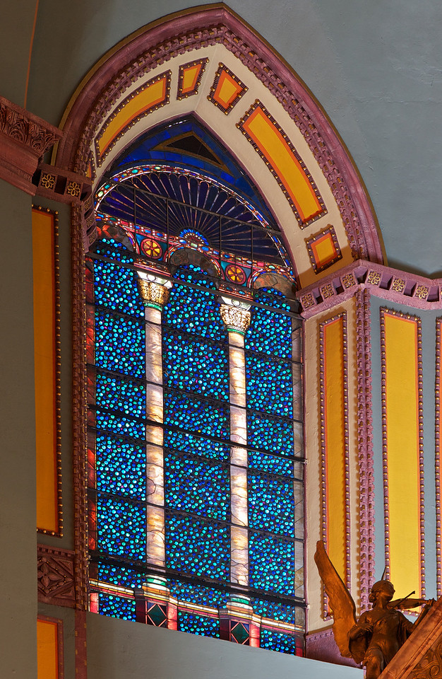 """Saint Paul the Apostle Chuch, Stained Glass Window Above the Altar by John LaFarge <br><br> LaFarge also did the windows that line the upper part of the church and the lancet windows in the choir loft. <br><br> John LaFarge (1835-1910) was an American painter, muralist, and stained glass window maker. He was born in New York City. Initially intending to study law, he changed his mind after visiting Paris in 1856. He studied with Thomas Couture. Another of Couture's students was Edouard Manet. See Couture's frescoes of the Virgin Mary in my gallery on Saint-Eustache. According to to <a href=""""http://en.wikipedia.org/wiki/John_LaFarge"""">Wikipedia, </a> LaFarge's earliest drawings and landscapes in Newport, Rhode Island (where he studied with painter William Morris Hunt) show originality, especially in the handling of color values.  <br><br> His first work in mural painting was in the Trinity Church in Boston in 1873. Aside from Saint Paul the Apostle, his other church works include the large altarpiece at the Church of the Ascension and Saint Paul's Chapel at Columbia University. He created four great lunettes (a half-moon shaped space) representing the history of law at the Minnesota State Capital and a similar series based on the theme of Justice for the State Supreme Court building in Baltimore, Maryland.  <br><br> He was a pioneer in the study of Japanese art.  """"LaFarge made extensive travels in Asia and the South Pacific, which inspired his painting. He visited Japan in 1886, and the South Seas in 1890 and 1891, in particular spending time and absorbing the culture of Tahiti. Henry Adams accompanied him on these trips as a travel companion. He visited Hawaii in September of 1890, where he painted scenic spots on Oahu and traveled to the Island of Hawaii to paint an active volcano. He learned several languages (ancient and modern), and was erudite in literature and art; by his cultured personality and reflective conversation, he influenced many other people. Though """