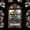 """Southward Cathedral, Harvard Chapel Stained Glass Window  <br><br> Founder of Harvard University John Harvard was born in near the church in Southwark. His father was a business associate of Shakespeare's family and Shakespeare is believed to have been present when John was baptized in the church in 1607, according to <a href=""""http://www.sacred-destinations.com/england/london-southwark-cathedral"""">Sacred Destinations.</a> <br><br> John Harvard is commemorated in the church by the Harvard Chapel, off the North Transept, restored with funds received from members of Harvard University. John was educated at Emmanuel College, Cambridge and graduated in 1635. """"The following year he married Anne Sadler and having no relatives left in Southwark, decided to join his brother Puritans to form a godly commonwealth in the New World. <br><br> Arriving in Boston, with his library of 320 volumes, Harvard was admitted a townsman of Charlestown and ministered in the 'First Church'. He was described as a scholar and lover of learning. He died childless in 1638. He left his books (of which only one remains) and half his fortune, £779 17s 2d, to the college of Newtown, a foundation for the 'education of English and Indian youth in knowledge and godliness'. Newtown became Cambridge, Massachusetts and the college became Harvard University <a href=""""http://cathedral.southwark.anglican.org/visit/area-2"""">according to the church website.</a> <br><br> Two panels of stained glass windows are the highlight of the chapel. The first is a window given by the then American Ambassador to London, Joseph Choate, in 1905.  Depicting the baptism of Christ by John the Baptist, it is by an American artist John La Farge. It uses a technique of mixing several colors in one piece of opalescent glass. The second shows the Harvard crest (Veritas, Latin for """"Verity"""" or """"Truth"""") and Emmanuel College, Cambridge with an inscription """"This Window, Damaged During World War 2 By Enemy Bombing, Was Restored In 1948 Throug"""