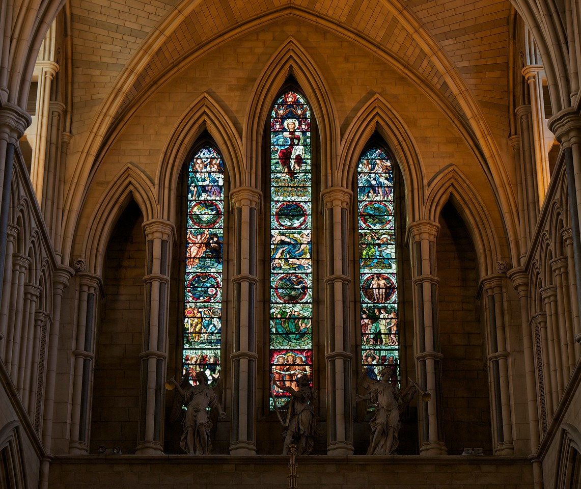 "Southwark Cathedral West Window Depicting Creation by Henry Holiday <br><br> The west window depicts Creation by Henry Holiday. The text under the creator in the center panel reads, ""In the beginning God created the heaven and the earth."" The text at the base of the center light is the response of created things: ""Oh, all ye works of the Lord, bless ye the Lord, praise Him, and magnify Him for ever."" <br><br> Christ is seated in the upper part of the central light and in His hand is the Universe with adoring Seraphim on either side with words ""Let the Heavens rejoice and the Earth be glad."" Cherubim with scrolls bear the words ""Holy, Holy, Holy, Lord God of Hosts."" <br><br> The center part of the three lights are represented by the six Days of Creation with each day enclosed in a circle. The first Day shows the Spirit of God moving upon the face of the waters; second Day shows a firmament dividing the waters above and below; third Day presents the division of Land and Water; fourth Day shows the creation of the heavenly bodies; fifth Day gives the waters bringing forth life; and the sixth Day presents Adam and Eve with a lion and an ox.  <br><br> I obtained information on this window from <a href=""http://books.google.com/books?id=GLwaAAAAYAAJ&pg=PA250&lpg=PA250&dq=southwark+cathedral+henry+holiday&source=bl&ots=zrg8OQbW4m&sig=wxuzfStD5blo-SS3gWygEIAeUDE&hl=en&sa=X&ei=Dls4U658pq6wBLKLgIgP&ved=0CE8Q6AEwCQ#v=onepage&q=southwark%20cathedral%20henry%20holiday&f=false"">Southwark Cathedral by William Thompson.</a>  <br><br> Thompson writes of the window: ""The details exhibit much originality of thought and treatment, and will amply repay the closest study. Ten minutes in the triforium passage, which runs in front of it, would not be time misspent. Opinions will differ widely as to the artistic merits and effectiveness of this window. The subject, on account of its vastness, was an extremely difficult one to treat in the narrow spaces of three lancet lights."" <br><br> Henry Holiday (1839-1927) was an English historical genre and landscape painter, stained glass designer, illustrator, and sculptor. He is considered to be a member of the Pre-Raphaelite school of art, according to <a href=""http://en.wikipedia.org/wiki/Henry_Holiday"">Wikipedia.</a> <br><br> Holiday was born in London and at age 15 was admitted to the Royal Academy. Through his friendship with several artists there, he was introduced to artists of the ""Pre-Raphaelite Brotherhood"". This movement was to be pivotal in his future artistic and political life. From Wikipedia: ""The group's intention was to reform art by rejecting what it considered the mechanistic approach first adopted by Mannerist artists who succeeded Raphael and Michelangelo. Its members believed the Classical poses and elegant compositions of Raphael in particular had been a corrupting influence on the academic teaching of art, hence the name ""Pre-Raphaelite""."" <br><br> In 1861, Holiday accepted the job of stained glass window designer for Powell's Glass Works. During his time there he fulfilled over 300 commissions, mostly for customers in the U.S. He left in 1891 to set up his own glass works in Hampstead, producing stained glass, mosaics, enamels and sacerdotal objects. <br><br> Holiday's stained glass work can be found all over Britain and some of his best is at Westminster Abbey according to Wikipedia. <br><br> In addition to his stained glass work, Holiday was a painter; his works include The Burgess of Calais, The Rhine Maiders, Dante and Beatrice. He was commissioned by Lewis Carroll to illustrate The Hunting of the Snark. He remained friends with the author throughout his life."