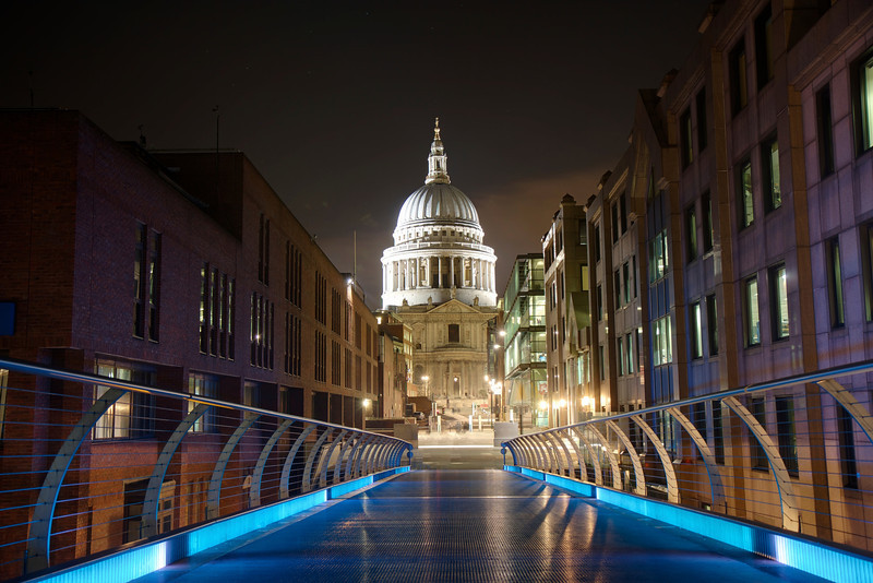 """Saint Paul's Cathedral from Millennium Bridge, London <br><br> Millennium Bridge, a footbridge across the River Thames between Southwark Bridge and Blackfriars Railway Bridge, provides a spectacular view of Saint Paul's Cathedral nested between two modern buildings and bridge supports. The <a href=""""https://www.stpauls.co.uk/"""">church website </a> has a photo on it's opening page, which sparked my interest in capturing the cathedral at night.  <br><br> Saint Paul's is one of the most visible and notable sights in London, dominating the skyline at the top of Ludgate Hill, the highest point in the City of London. Noted architect Sir Christopher Wren designed the church in the English Baroque style. Wren designed more than 50 London churches after the Great Fire of 1666. The church was consecrated in 1697.  <br><br> Herbert Mason's photograph of the cathedral dome surrounded by smoke from German bombing during the Battle of Britain is an iconic image symbolizing Britain's defiance of Nazi tyranny. The resilient church withstood the bombing; a German time-delayed bomb hit the cathedral in September 1940 and was diffused and removed by a bomb squad. According to <a href=""""http://en.wikipedia.org/wiki/St_Paul%27s_Cathedral"""">Wikipedia, </a> the bomb would have destroyed the church, as it left a 100 foot crater when later detonated in a secure location.   <br><br> Important services held at St Paul's have included the funerals of Lord Nelson, the Duke of Wellington, Sir Winston Churchill, and Margaret Thatcher; Jubilee celebrations for Queen Victoria; peace services marking the end of the First and Second World Wars; the wedding of Charles, Prince of Wales, and Lady Diana Spencer, and the launch of the Festival of Britain, according to <a href=""""http://en.wikipedia.org/wiki/St_Paul%27s_Cathedral"""">Wikipedia. </a>"""