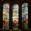 """Saint Michael's Victory in Heaven by Louis Comfort Tiffany <br><br> I summarized information on the Tiffany windows from a pamphlet available in the narthex (entrance) of the church, """"A Brief Tour and Description of St. Michael's Church Interior and Windows,"""" by church Archivist Jean Ballard Terepka.  <br><br> After completion of the building in 1891, Saint Michael's rector, John Punnett Peters embarked on furnishing and decorating the church, turning to the Tiffany Glass and Decorating Company for much of the work. On Christmas Day 1895, the Tiffany windows """"Saint Michael's Victory in Heaven"""" were dedicated.  <br><br> Each of the windows is five by 25 feet. The seven panels depict the victor of Saint Micheal in heaven from Revelation 12:7-12 where Satin is expelled from heaven. Saint Michael """"…the great archangel, stands on a globe among the clouds, is clothed in armor, and brandishes a sword in one hand. He bears a banner with a cross in the other hand, showing that he stands for Christ. The other archangels are Gabriel, Raphael, Uriel, Enogh, Barachiel, Jehudiel and Sealtahiel. They are surrounded by the angel hosts playing many musical instruments and singing praises to God. This window is considered the finest composition in American favrile glass,"""" and was designed by Louis Comfort Tiffany.  As described by Terepka, favrile glass is an American invention from the late 19th century. In this process only the face and hands are painted. Everything else constructed of pieces of colored glass fitted into and over one another to give the proper colors, shades, and forms. Wikipedia describes it as follows: """"Favrile glass is a type of iridescent art glass designed by Louis Comfort Tiffany. It was patented in 1894 and first produced in 1896. It differs from most iridescent glasses because the color is ingrained in the glass itself, as well as having distinctive coloring. Favrile glass was used in Tiffany's stained-glass windows."""""""