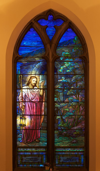 """The Second Reformed Church Christ, Christ, Knocking at the Door Window <br><br> From <a href=""""http://www.secondreformed.org/stainedglass"""">the church website:</a> <br><br> """"Our hearts need to be opened to let Jesus enter. The lantern Jesus carries is symbolic of His being the Light of the World. This lantern radiates its light on the darkest day!  <br><br> This was a very popular theme of the period and Tiffany Studios installed many windows similar to this one. The studios utilized this basic design concept and customized it for other churches. A variation was the addition of a crown to Jesus' head. Colors would have been coordinated to harmonize with the surroundings in each location."""" <br><br> Louis Comfort Tiffany (1848-1933) was one of America's most acclaimed artists and is most associated with the Art Nouveau and Aesthetic movements according to <a href=""""http://en.wikipedia.org/wiki/Louis_Comfort_Tiffany"""">Wikipedia.</a> He focused in the decorative arts and is best known for his work in stained glass. He was the son of Charles Lewis Tiffany (1812-1902), founder of Tiffany & Company. Lewis chose to pursue his own artistic interests rather than joining the family business.  <br><br> He began his career as a painter and traveled extensively through Europe. In the late 1870s, Tiffany turned his attention to decorative arts and interiors. In 1881, he did the interior design of the Mark Twain House in Hartford Connecticut. His most notable work was in 1862 when President Chester Arthur refused to move into the White House until it had been resorted, according to Wikipedia. He commissioned Tiffany, who had begun to make a name for himself for interior design work, to redo the state rooms. Tiffany worked on the East Room, Blue Room, Red Room, the State Dining Room, and the Entrance Hall.  <br><br> From  <a href=""""http://www.metmuseum.org/toah/hd/tiff/hd_tiff.htm"""">The Metropolitan Museum website:</a> """"By late 1892 or early 1893, Tiffany built a glasshouse in Corona, Que"""