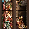 """Victory Over Death by Frederick Wilson of Tiffany Glass Company <br><br> This window depicts Martha, Mary, and Jesus at the tomb of Lazarus. Above them are angels heralding victory over death and a flock of doves in flight, symbolizing departed souls seeking God. The window was designed by Frederick Wilson, the leading designer (after Tiffany himself) at the Tiffany Glass Company, according to the <a href=""""http://www.churchoftheincarnation.org/about-incarnation/landmark-building/the-window-tour/victory-over-death-13/"""">Incarnation website.</a> <br><br> """"Note that in the American-manufactured windows in this church, the faces and portraits are painted in oils onto the transparent glass. The English-manufactured windows in this church use an entirely different technique, where all aspects of the illustration are etched directly onto the colored glass and stained prior to assembly. The painted portraits have weathered over time, and are now protected from weather elements with a outer layer of plexiglass."""" <br><br> Louis Comfort Tiffany (1848-1933) was one of America's most acclaimed artists and is most associated with the Art Nouveau and Aesthetic movements according to <a href=""""http://en.wikipedia.org/wiki/Louis_Comfort_Tiffany"""">Wikipedia.</a> He focused in the decorative arts and is best known for his work in stained glass. He was the son of Charles Lewis Tiffany (1812-1902), founder of Tiffany & Company. Lewis chose to pursue his own artistic interests rather than joining the family business.  <br><br> He began his career as a painter and traveled extensively through Europe. In the late 1870s, Tiffany turned his attention to decorative arts and interiors. In 1881, he did the interior design of the Mark Twain House in Hartford Connecticut. His most notable work was in 1862 when President Chester Arthur refused to move into the White House until it had been resorted, according to Wikipedia. He commissioned Tiffany, who had begun to make a name for himself for interior"""