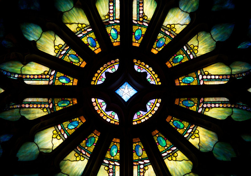 "The Second Reformed Church Rose Window <br><br> From <a href=""http://www.secondreformed.org/stainedglass"">the church website</a> <br><br> ""When our current building was built, Tiffany was commissioned to create this beautiful window which is very interactive during morning worship. Sometimes the deep olive green predominates. Some days a beautiful blue is seen at the outer edge. Other days when the sunlight strikes it directly, it is golden and so radiant that the star in the center is not able to be seen. <br><br> The Metropolitan Museum of Art noted at the time of the installation in 1909, ""...under the personal supervision of Mr. Louis C. Tiffany, has been placed in the Church-'a magnificent Rose Window containing a jeweled cross, extending through many openings in the circle with an illuminated background representing the sky'""."" <br><br> Louis Comfort Tiffany (1848-1933) was one of America's most acclaimed artists and is most associated with the Art Nouveau and Aesthetic movements according to <a href=""http://en.wikipedia.org/wiki/Louis_Comfort_Tiffany"">Wikipedia.</a> He focused in the decorative arts and is best known for his work in stained glass. He was the son of Charles Lewis Tiffany (1812-1902), founder of Tiffany & Company. Lewis chose to pursue his own artistic interests rather than joining the family business.  <br><br> He began his career as a painter and traveled extensively through Europe. In the late 1870s, Tiffany turned his attention to decorative arts and interiors. In 1881, he did the interior design of the Mark Twain House in Hartford Connecticut. His most notable work was in 1862 when President Chester Arthur refused to move into the White House until it had been resorted, according to Wikipedia. He commissioned Tiffany, who had begun to make a name for himself for interior design work, to redo the state rooms. Tiffany worked on the East Room, Blue Room, Red Room, the State Dining Room, and the Entrance Hall.  <br><br> From  <a href=""http://www.metmuseum.org/toah/hd/tiff/hd_tiff.htm"">The Metropolitan Museum website:</a> ""By late 1892 or early 1893, Tiffany built a glasshouse in Corona, Queens, New York, and, with Arthur Nash, a skilled glassworker from Stourbridge, England, his furnaces developed a method whereby different colors were blended together in the molten state, achieving subtle effects of shading and texture. Recalling the Old English word fabrile (hand-wrought), Tiffany named the blown glass from his furnaces Favrile, a trademark that signified glass of hand-made and unique quality."" <br><br> ""Of all of Tiffany's artistic endeavors, leaded-glass brought him the greatest recognition. Tiffany and his early rival, John La Farge, revolutionized the look of stained glass, which had remained essentially unchanged since medieval times when craftsmen utilized flat panes of white and colored glass with details painted with glass paints before firing and leading. Tiffany and La Farge experimented with new types of glass and achieved a more varied palette with richer hues and greater density. By 1881, each had patented an opalescent glass, a unique American phenomenon that featured a milky, opaque, and sometimes rainbow-hued appearance with the introduction of light. Internally colored with variegated shades of the same or different hues, Tiffany's Favrile glass enabled craftsmen to substitute random tonal gradations, lines, textures, and densities inherent in the material itself for pictorial details."" <br><br> At its peak, his factory employed over 300 artisans. He was appointed as art director at Tiffany & Company upon his father's death in 1902. <br><br> Tiffany lived during the Gilded Age, a period of rapid church expansion; one source reports that there were 4,000 churches under contraction in the U.S. in the 1880s according to a recent <a href=""http://www.nytimes.com/2013/01/01/arts/design/louis-c-tiffany-works-at-museum-of-biblical-art.html?ref=louiscomforttiffany"">The New York Times article</a> on an exhibit of Tiffany's ecclesiastical work. There was a great demand for artists that could create great and inspiring stained glass windows, mosaics, rederos, and altars. Many churches turned to Tiffany to create such beautiful works. His work in New York churches include Saint Michaels, Advent Lutheran, Saint Ignatius Loyola, Temple Emmanu-El, Church of the Incarnation, Holy Trinity Lutheran Church, Eldridge Street Synagogue; in New Jersey, numerous windows are in Second Reformed Church of Hackensack. <br><br> After fire destroyed their first church, The Second Reform Church in Hackensack, New Jersey contacted Tiffany requesting windows depicting events in the life of Christ and contracted Tiffany Studios for five windows, according to <a href=""http://www.secondreformed.org/clientimages/42874/stainedglasswindows/stained%20glass%20window%20info.pdf"">the church website.</a> The church also contracted Duffner & Kimberly Co. for one window.  The installation of these windows was competed before the dedication ceremony in 1909.  <br><br> From the church website: <br><br> ""The New York Times (May 4, 1979) wrote: ""Some of Tiffany's favorite windows are in the Second Reformed Church in Hackensack ,... Tiffany frequently visited there with clients in tow, using  the visit to help them select appropriate design for their purposes."" For each installation, the design was customized as the client requested and reworked to fit the window's opening size and shape requirements. Colors were coordinated to harmonize with the surroundings in each location."""