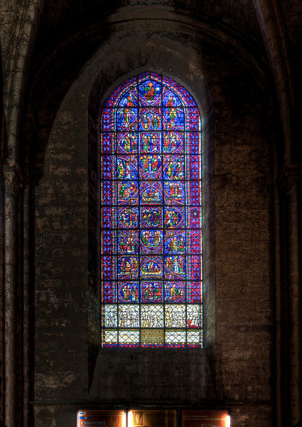 "Chartres Appollinare Window <br><br> The brilliant blue and red glass in one window in the south transept stunned me. This was my favorite window and I stared at it for 15 minutes, trying to figure out the story without success. Also, there is an inscription at the bottom that I couldn't read.  <br><br> At home, I found a great website that describes the windows and statues at Chartres from <a href=""http://digital.library.pitt.edu/c/chartres/"">Alison Stones</a>, a Professor of History of Art and Architecture at the University of Pittsburgh with a detailed discussion <a href=""http://www.medart.pitt.edu/image/France/Chartres/Chartres-Cathedral/Windows/Nave-windows/36-Apollinaire/CHARTRES-36Apoll-main.HTM"">of this window.</a> From the website, this window is Apollinare and the Choirs of Angels depicting the life of Apollinare. Saint Apollonaris (Apollinare in Italian), a native of Antioch became the first bishop of Ravenna and Classe and who was martyred for his faith. On the left side, fourth full square from the top shows Apollinare being beaten and the next square depicts the funeral. The panels above represent the Choirs of Angels. Christ in Majesty is the very top center panel. The website provides a photo of each of the panels along with rich detail.  <br><br> I made several exposures from -2 to 2 stops, ranging from 0.8 seconds to 10 seconds, f7.1, 100 ISO. For the walls, the image that best captured the dirt and grime from 800 years was the property exposed image. The best image of the window came from the photo that was one stop underexposed. I cut and pasted the window from that version onto the other image. I then used PTLens to pull the top of the image forward, eliminating barrel distortion."