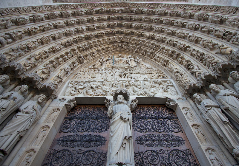 "Notre Dame Center West Portal <br><br> Standing outside the center of the west portal of Notre Dame, I had a strange feeling that a lot of people were looking at me in judgment. No wonder as this portal depicts the Last Judgment, originally sculpted between 1200 and 1240. Unfortunately many statues, particularly the large jamb statues (the first carved figures a visitor meets on a visit to a Gothic cathedral-traditionally depicting Old Testament prophets or martyred saints), were destroyed in the Revolution. During the major restoration campaign in the mid-1800s, Eugène Emmanuel Viollet-le-Duc restored the portal to its original state by replacing trumeau (a pillar in the center of a Gothic portal) and jamb statues. The trumeau shows Christ teaching. Just above Christ's head is the lower lintel of the tympanum (a panel above a main portal, or doorway, usually heavily decorated) the Resurrection of the Dead. Here the dead emerge from their tombs at the sound of the angels' trumpets. Just above is the Weighing of Souls by the Archangel Michael, with a furry Devil's interference. To the right are the Dammed and to the left are the Redeemed. Above that in the tympanium is Christ in Majesty. Christ displays his wounds, flanked by angels. The kneeling figures are the Virgin Mary and St. John, who were present at the crucifixion. The right jamb figures features Apostles Paul, James the Great, and Thomas. The left jamb consists of statues of Bartholomew, Simon, and James the Less. Above the right jamb statues are interesting figures of the torments of the damned in hell. For much more detail, see <a href=""http://www.sacred-destinations.com/france/paris-notre-dame-last-judgment-portal.htm"">Sacred Destinations</a> and <a href=""http://www.notredamedeparis.fr/spip.php?article409"">Norte Dame's website.</a> <br><br> To get a unique perspective of the Portal, I used a wide angle lens with a focal length equivalent of 16mm positioned very close to the Portal, looking up.  I did not do much work on the image, simply straightened it out using PTLens and cropped it so the right side matched the left side."