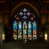 "Christ the King Stained Glass West Window by Henry Holiday <br><br><a href=""http://www.holytrinity-nyc.org/stained-glass-windows/"">From the Holy Trinity website:</a>  <br><br> ""20 feet by 15 with a stony arch-like frame, the west window has 15 panels divided into three rows of five columns each. <br><br> The bottom row are representations of our earthly life and the middle row life in heaven or paradise.  On the bottom row, from left to right, the first panel represents philosophy and poetry with a man holding a piece of parchment and the woman standing by his side and holding a stringed instrument.  The next panel is science and agriculture portrayed by a man holding a telescope and a man and woman grasping firmly some agrarian implements.  The central panel is the church and government represented by a man in ecclesiastical garb and a king and queen.  <br><br> The fourth panel symbolizes art and industry with an artist sitting with his brush and painting board; industry is shown by a woman holding some flax and a man clasping a hammer and some steel.  The last panel is of music and mathematicsóa young woman is playing a violin while at her side sits a young man with ruffled brow and in his hands a long paper covered with geometrical figures. <br><br> The middle row pictures men, women and children strolling happily in a sort of Garden of Eden. <br><br> The top row of panels shows Jesus sitting, clothed in the robes of a ruling king, and holding the orb, the symbol of power.  His angelic helpers stand on either side of the throne. <br><br> The highest part of the window, in the shape of a large four-leaf clover, has four small rosette windows each picturing a knight clad in armor."" <br><br> There are 17 stained glass windows created by Henry Holiday of London, all memorials to various members of the Rhinelander family. Holiday made all 17 except for the west window, which was completed by his daughter after his death. The windows are the only complete cycle of windows remaining by Holiday, and the church is one of a few churches in the world in which all windows are designed by one artist, according to church website. <br><br> Henry Holiday (1839-1927) was an English historical genre and landscape painter, stained glass designer, illustrator, and sculptor. He is considered to be a member of the Pre-Raphaelite school of art, according to <a href=""http://en.wikipedia.org/wiki/Henry_Holiday"">Wikipedia.</a> <br><br> Holiday was born in London and at age 15 was admitted to the Royal Academy. Through his friendship with several artists there, he was introduced to artists of the ""Pre-Raphaelite Brotherhood"". This movement was to be pivotal in his future artistic and political life. From Wikipedia: ""The group's intention was to reform art by rejecting what it considered the mechanistic approach first adopted by Mannerist artists who succeeded Raphael and Michelangelo. Its members believed the Classical poses and elegant compositions of Raphael in particular had been a corrupting influence on the academic teaching of art, hence the name ""Pre-Raphaelite""."" <br><br> In 1861, Holiday accepted the job of stained glass window designer for Powell's Glass Works. During his time there he fulfilled over 300 commissions, mostly for customers in the U.S. He left in 1891 to set up his own glass works in Hampstead, producing stained glass, mosaics, enamels and sacerdotal objects. <br><br> Holiday's stained glass work can be found all over Britain and some of his best is at Westminster Abbey according to Wikipedia. <br><br> In addition to his stained glass work, Holiday was a painter; his works include The Burgess of Calais, The Rhine Maiders, Dante and Beatrice. He was commissioned by Lewis Carroll to illustrate The Hunting of the Snark. He remained friends with the author throughout his life."