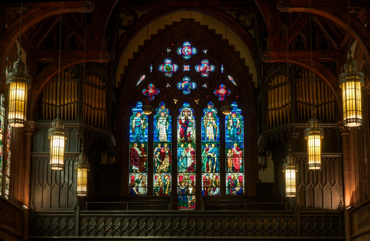 """Christ the King Stained Glass West Window by Henry Holiday <br><br><a href=""""http://www.holytrinity-nyc.org/stained-glass-windows/"""">From the Holy Trinity website:</a>  <br><br> """"20 feet by 15 with a stony arch-like frame, the west window has 15 panels divided into three rows of five columns each. <br><br> The bottom row are representations of our earthly life and the middle row life in heaven or paradise.  On the bottom row, from left to right, the first panel represents philosophy and poetry with a man holding a piece of parchment and the woman standing by his side and holding a stringed instrument.  The next panel is science and agriculture portrayed by a man holding a telescope and a man and woman grasping firmly some agrarian implements.  The central panel is the church and government represented by a man in ecclesiastical garb and a king and queen.  <br><br> The fourth panel symbolizes art and industry with an artist sitting with his brush and painting board; industry is shown by a woman holding some flax and a man clasping a hammer and some steel.  The last panel is of music and mathematicsóa young woman is playing a violin while at her side sits a young man with ruffled brow and in his hands a long paper covered with geometrical figures. <br><br> The middle row pictures men, women and children strolling happily in a sort of Garden of Eden. <br><br> The top row of panels shows Jesus sitting, clothed in the robes of a ruling king, and holding the orb, the symbol of power.  His angelic helpers stand on either side of the throne. <br><br> The highest part of the window, in the shape of a large four-leaf clover, has four small rosette windows each picturing a knight clad in armor."""" <br><br> There are 17 stained glass windows created by Henry Holiday of London, all memorials to various members of the Rhinelander family. Holiday made all 17 except for the west window, which was completed by his daughter after his death. The windows are the only complete cycle of wind"""