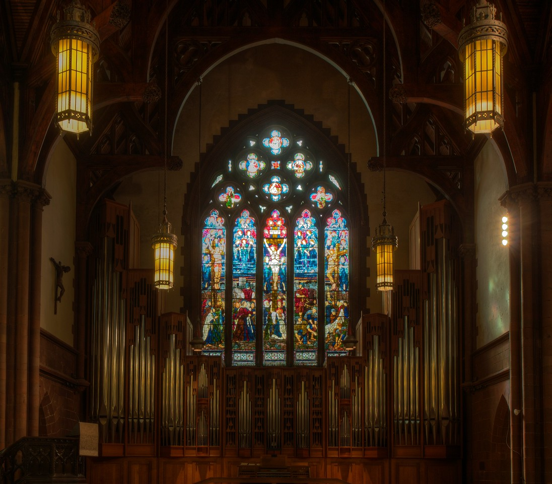 """Holy Trinity Episcopal Church Organ by Rieger-Orgelblau and Stained Glass Windows by Henry Holiday <br><br> The pipe organ in the south transept was designed and constructed by Rieger-Orgelblau of Austria and installed in 1987. The company started in 1845 <a href=""""http://www.rieger-orgelbau.com/en/"""">According to the company website.</a>  <br><br><a href=""""http://en.wikipedia.org/wiki/Rieger_Orgelbau"""">Wikipedia</a> has a list of notable Rieger organs.  <br><br><a href=""""http://www.holytrinity-nyc.org/stained-glass-windows/"""">From the Holy Trinity website on The Crucifixion south transept window:</a>  <br><br> """"In the main panel Jesus is seen fixed to the cross with the two thieves who were crucified with him on either side.  On the left side Mary Magdalene, Mary, the mother of Jesus and Solome, the mother of James and John.  In the lower right hand of the picture a group of Roman soldiers are shown casting lots for the garments of Christ.  <br><br> John 19:23  When the soldiers had crucified Jesus they took his garments and made four parts, one for each soldier; also his tunic.  But the tunic was without seam, woven from top to Bottom; so they said to one another, """"Let us not tear it, but cast lots for it to see whose it shall be.""""  This was to fulfill the scripture, """"They parted my garments among them, and for my clothing they cast lots."""" <br><br> The whole scene is surmounted by a host of angels praying and waiting to receive the soul of the crucified Christ. <br><br> In the tracery above the main portion of the window, there is a small window containing the symbol ìXPî, the abbreviation of Christís name in Greek.  There are also four small cloverleaf windows which continue the story after the crucifixion.  From the left to the right they portray Christ being taken down from the cross; Christ being placed in the he tomb; a soldier standing guard; and finally, Martha and Mary bringing spices for Christís body. <br><br> Matthew 27:57  When it was evening, there came a r"""