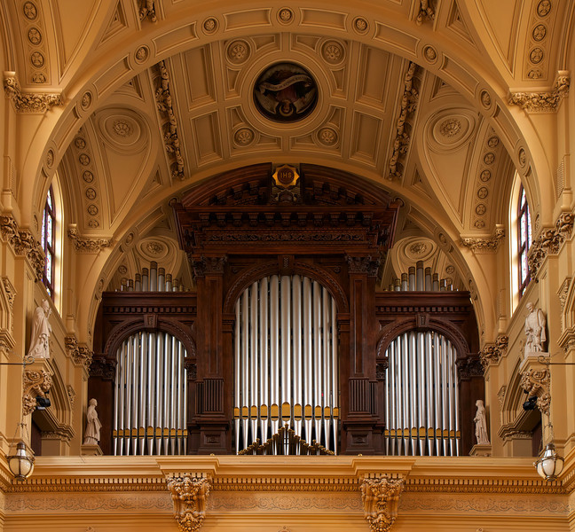 "The Church of Saint Xavier Organ <br><br> From <a href=""http://www.nycago.org/Organs/NYC/html/StFrancisXavier.html"">NYCAGO.org</a>: <br><br> ""As part of its restoration campaign, the church contracted with the Peragallo Pipe Organ Company of Paterson, N.J., to build a new organ. Completed in 2010, Peragallo's Opus 700 is a hybrid organ that combines a total of 52 ranks of pipes—including 23 ranks from the previous Kilgen gallery organ—with several digital stops. The organ was designed with a French tonal scheme by John Peragallo III, Tonal Director of the company, in consultation with John Uehlein, Director of Music. <br><br> The main instrument is installed in two chambers that were created in the triforium on each side of the chancel. Fronting the four tone openings into the chancel and transepts are oak cases with façades of functional pipes that have gothic gold arched mouths. Frank Peragallo designed the case work. The Grand-Orgue, Grand-Choeur and Pédale divisions are located in the east (liturgical north) chamber and the Récit and Positif divisions are in the west (liturgical south) chamber. The Antiphonale division at the rear of the church is comprised of eight digital stops that emanate from behind the original organ case plus the 49 gold-painted pipes of the Trompette en chamade that are mounted at the base of the case. Built in 1881 by E. & G.G. Hook & Hastings of Boston, the noble hand-carved organ case was restored and its façade pipes were painted silver with gold mouths. Controlling the organ is a movable three-manual French-style console with terraced drawknobs and a hand-carved music rack that incorporates the Xavier cross. A complete MIDI interface and sound module allows the organist to access many digital effects for contemporary worship music and record and playback the instrument. <br><br> The organ was dedicated on October 11, 2010, with a recital by organist Matthew Phelps, assisted by mezzo-soprano Robin Lynne Frye."""