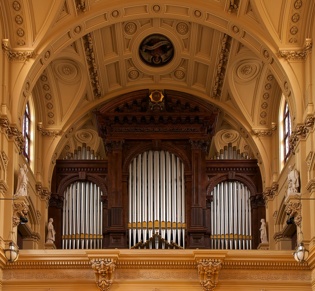 """The Church of Saint Xavier Organ <br><br> From <a href=""""http://www.nycago.org/Organs/NYC/html/StFrancisXavier.html"""">NYCAGO.org</a>: <br><br> """"As part of its restoration campaign, the church contracted with the Peragallo Pipe Organ Company of Paterson, N.J., to build a new organ. Completed in 2010, Peragallo's Opus 700 is a hybrid organ that combines a total of 52 ranks of pipes—including 23 ranks from the previous Kilgen gallery organ—with several digital stops. The organ was designed with a French tonal scheme by John Peragallo III, Tonal Director of the company, in consultation with John Uehlein, Director of Music. <br><br> The main instrument is installed in two chambers that were created in the triforium on each side of the chancel. Fronting the four tone openings into the chancel and transepts are oak cases with façades of functional pipes that have gothic gold arched mouths. Frank Peragallo designed the case work. The Grand-Orgue, Grand-Choeur and Pédale divisions are located in the east (liturgical north) chamber and the Récit and Positif divisions are in the west (liturgical south) chamber. The Antiphonale division at the rear of the church is comprised of eight digital stops that emanate from behind the original organ case plus the 49 gold-painted pipes of the Trompette en chamade that are mounted at the base of the case. Built in 1881 by E. & G.G. Hook & Hastings of Boston, the noble hand-carved organ case was restored and its façade pipes were painted silver with gold mouths. Controlling the organ is a movable three-manual French-style console with terraced drawknobs and a hand-carved music rack that incorporates the Xavier cross. A complete MIDI interface and sound module allows the organist to access many digital effects for contemporary worship music and record and playback the instrument. <br><br> The organ was dedicated on October 11, 2010, with a recital by organist Matthew Phelps, assisted by mezzo-soprano Robin Lynne Frye."""""""