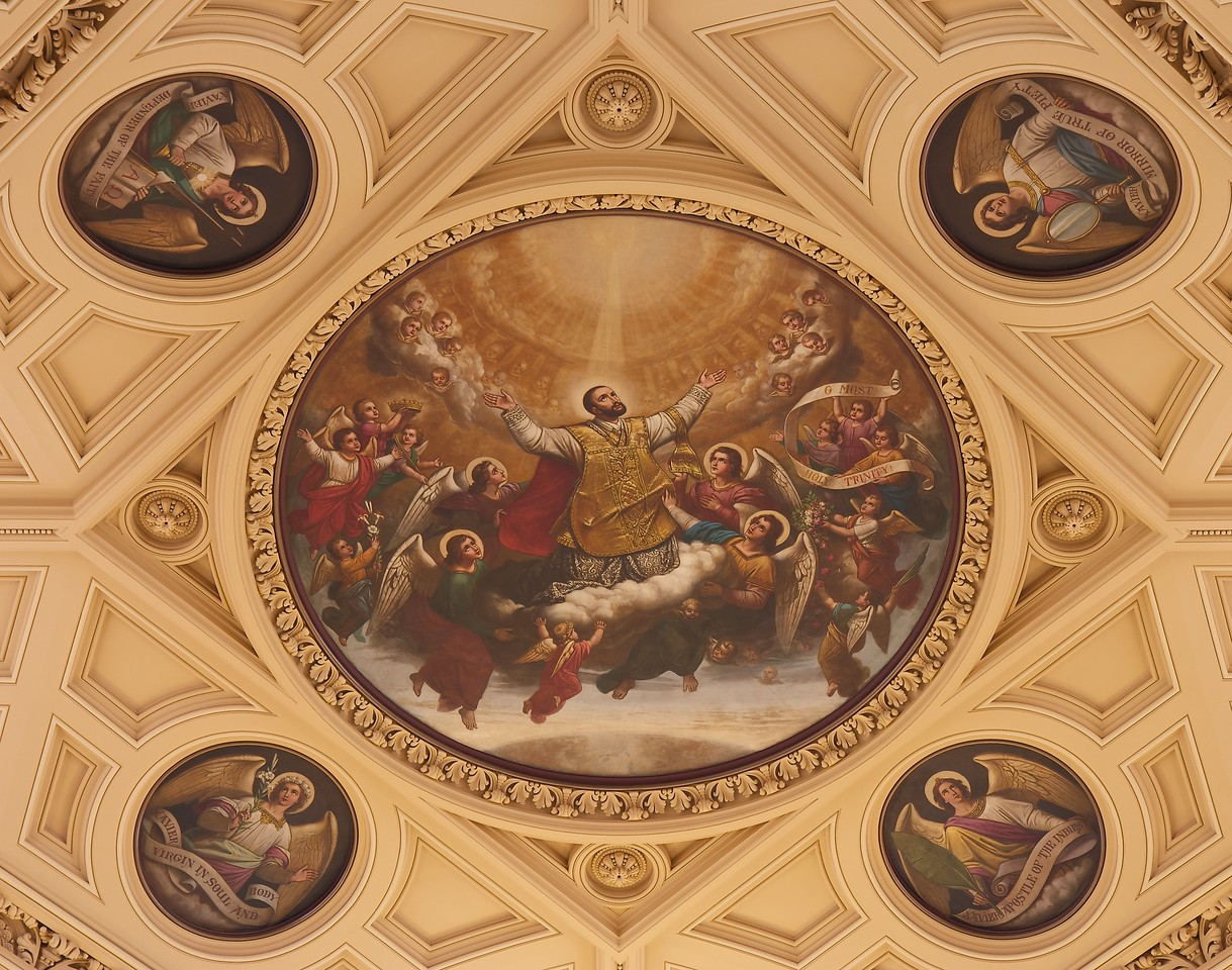 """The Church of Saint Francis Xavier, The Apotheosis of St. Francis Xavier <br><br> From the <a href=""""http://www.sfxavier.org/wordpress/wp-content/uploads/downloads/2013/02/Entire-Tour-Guide-Reduced.pdf """">Church of St. Francis Xavier Tour Guide</a> available at the church website and at the church entrance: <br><br> """"The large central medallion, The Apotheosis of St. Francis Xavier, above the altar area depicts St. Francis Xavier born heavenward by angels. The four lesser medallions include angels carrying scrolls representing his virtues: <br><br> A green palm of victory for Xavier, Apostle of the Indies A lily of chastity of Xavier, Virgin in Soul and Body A cross and chalice for Defender of the Faith A mirror in hand for Mirror of True Piety"""""""