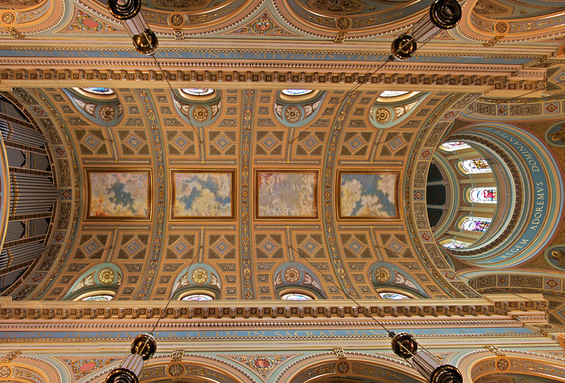"Saint Jean Baptiste Catholic Church Dome and Vaulted Ceiling <br><br> The ceiling at Saint Jean's is spectacular and a number of my photos emphasize the upper levels of the church. The massive ceiling is beautifully done in bright colors with ornate plasterwork throughout. This photo a panorama consisting of three stitched exposures using a Canon 10-22mm lens at 10 mm (16mm with 1.6X crop factor) mounted on a tripod near the floor at f6.3, 100 ISO, 5 seconds.  <br><br> From the<a href=""http://stjeanbaptisteny.org/History/Architectural-Tour""> Saint Jean Baptiste website,</a> number 10: <br><br> ""Rising high above the floor of the nave, the dome and the vaulted ceiling presented many challenges to the restorers in the late 1990s, not the least of which was the choice of colors.  Ultimately, fifteen colors were chosen: blues, browns, golds, greens, and purples, all derivative of the permanent features of the church. <br><br> The ceiling is adorned with six illusionistic panels that open to the sky as the realm of God.  The ornate plasterwork along the bands of the ceiling includes various symbols of the Eucharist and heavenly abundance (wheat, grapes, peacocks, and cornucopia).  Ceiling wreaths laden with fruit echo these themes.  The cornice, which wraps around the church just above the pillars, is decorated with acanthus leaves and florets and with cameo portraits of the founders of the two religious orders that serve Saint Jean Baptiste ― Saint Marguerite Bourgeoys of the Congregation of Notre Dame and Saint Peter Julian Eymard of the Congregation of the Blessed Sacrament.  Excerpts from the Latin text of Saint Thomas Aquinas' stirring Eucharistic hymn, Lauda Sion, in elegant gold lettering, encircle the seating area and the sanctuary."""