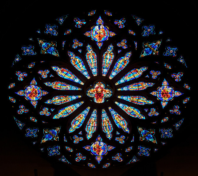 "Saint John the Divine Great Rose Window by Charles Connick (1933) <br><br> According to material from the church, Charles Connick designed the Great Rose Window in 1933. ""Christ is surrounded by angels, beatitudes, the four evangelists (Matthew, Mark, Luke, John), the prophets (Isiah, Jeremiah, Daniel and Ezekiel), Divine Love, Seraphim and Divine Wisdom: Cherubim."" <br><br> This is one of the first photos I took with a long telephoto lens, a Canon 70-200 f4 USM. My work up to that point was with much wider angle lenses, 10-22mm or 17-55mm, which provides a nice overall view of a window. However, I wanted a much closer perspective, tight enough to see the artist's detail of the work. Considering the 1.6X crop factor, this was shot at 112mm.  <br><br> Charles Connick (1875–1945) was a prominent artist best known for his work in stained glass in the Gothic Revival style. He was born in Crawford Country, Pennsylvania and developed an interest in drawing at an early age. He left high school when his father became disabled to become an illustrator on the staff of the Pittsburgh Press. At the age of 19, he learned the art of stained glass as an apprentice in the shop of Rudy Brothers in Pittsburgh, where he stayed through 1899. He worked for a number of stained glass companies in Pittsburgh and New York. He went to England and France to study ancient and modern stained glass, including those in the Chartres Cathedral. His first major work was First Baptist Church in Pittsburgh in 1912. Connick settled in Boston opening a stained glass studio in Back Bay in 1913; the Charles J. Connick Associates Studio continued to operate after his death until 1986. He produced many notable windows in such churches as Saint Patrick's Cathedral, Saint John the Divine, the Princeton University Chapel, and Saint Vincent Ferrer. According to Wikipedia, the Charles J. Connick Associates Studio produced some 15,000 windows in more than 5,000 churches and public buildings. <br><br> According to <a href=""http://en.wikipedia.org/wiki/Charles_Connick"">Wikipedia, </a> ""Connick preferred to use clear ""antique"" glass, similar to that of the Middle Ages and praised this type of glass as ""colored radiance, with the lustre, intensity, and baffling vibrant quality of dancing lights."" He employed a technique of ""staggered"" solder-joints in his leading and bars, which English stained-glass historian Peter Cormack says gives the windows their ""syncopated or 'swinging' character."" His style incorporated a strong interest in symbolism as well. Connick expressed the opinion that stained glass's first job was to serve the architectural effect and he believed that his greatest contribution to glasswork was ""rescuing it from the abysmal depth of opalescent picture windows"" of the sort popularized by Louis Comfort Tiffany and John La Farge. Although firmly committed to a regenerated handicraft tradition, Connick welcomed innovation and experimentation in design and technique among his co-workers at his studio."" <br><br> According to the <a href=""http://www.cjconnick.org/"">Charles J. Connick Stained Glass Foundation website</a> ""Using pure, intense color and strong linear design, this guild of artists led the modern revitalization of medieval stained glass craftsmanship in the United States.  Their work reflected a strong interest in symbolism in design and color, and stressed the importance of the relationship between the window's design and its surrounding architecture.  As if with one mind and one pair of hands, the craftsmen in the Connick Studio worked collectively on their windows like the 12th- and 13th- century artisans whose craft inspired them."" <br><br> The Charles J. Connick Stained Glass Foundation was formed after the studio closed in 1986. According to the <a href=""http://www.cjconnick.org/"">foundation website</a> ""The mission of the Charles J. Connick Stained Glass Foundation, Ltd. is to promote the true understanding of the glorious medium of color and light and to preserve and perpetuate the Connick tradition of stained glass."" <br><br> Here is an interesting <a href=""http://video.mit.edu/watch/charles-j-connick-and-mit-10153/"">video from the Massachusetts Institute of Technology</a> on Connick. In December 2008, the foundation donated materials to the MIT's Rotch Library of Architecture and Planning to form the Charles J. Connick Stained Glass Foundation Collection."