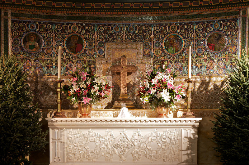 "Saint Michael's Altar and Reredos by Louis Comfort Tiffany <br><br> From a pamphlet available in the narthex (entrance) of the church, ""A Brief Tour and Description of St. Michael's Church Interior and Windows,"" by church Archivist Jean Ballard Terepka: <br><br> ""Reredos is from two Latin-French words meaning rear and back. The reredos behind the High Altar is in the form of a mosaic set against and into the wall. It contains four medallions representing a winged man, a winged lion, a winged bull and an eagle; each holds a book. These are the four cherubim described in Ezekiel I & I ad the four beasts or creatures of Revelation IV and V. In Christian art, they also represent the four evangelists, Matthew, Mark, Luke and John, who proclaim to the world Jesus Christ as the revelation of God in the world.  <br><br> The High Altar is of white marble, framed in a rich yellow marble, set against a dark background in order to make it the most conspicuous object in the church. In the center is a square cross constructed of circles running into one another. In the fields at the angles of the cross are inscribed in Greek the first and last letter of Jesus and Christ , ""IΣ"" and ""X Σ"" (IS and XS) and the Greek acronym, ""NI-KA"" (i.e., Jesus Crhist conquers by the Cross). In the long panels at the corners of the altar, and on both ends, is depicted the victory of the cross by the cross standing on the world. Between the cross in the center and the crosses in the corners, is a triangle of smaller circles and combining with the Triangles of the Trinity."""