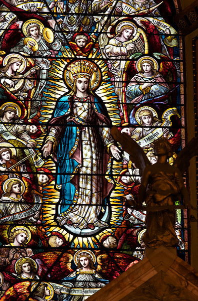 "High Altar Stained Glass Windows by Mayer & Co. of Munich <br><br> These beautiful stained glass windows above the altar were made by Mayer & Co. of Munich, now known as Franz Meyer of Munich, Inc. The firm is famous for stained glass design and manufacturing. Founded in 1847, the firm was popular in the late 19th and early 20th centuries for providing stained glass to large Roman Catholic churches constructed during that period. <a href=""http://en.wikipedia.org/wiki/Franz_Mayer_%26_Co."">Wikipedia</a> provides a long list of churches that feature Mayer stained glass windows throughout the world.  <br><br> The company still exists and the New York Mass Transit Authority is one client. Franz Meyer mosaics can be found at the South Ferry, 86th Street, 42nd Street and 8th Ave., Penn Station, and Bryant Park subway stations just to name a few. For more detail on their work, see the <a href=""http://www.mayer-of-munich.com/""> Franz Meyer company website.</a>"