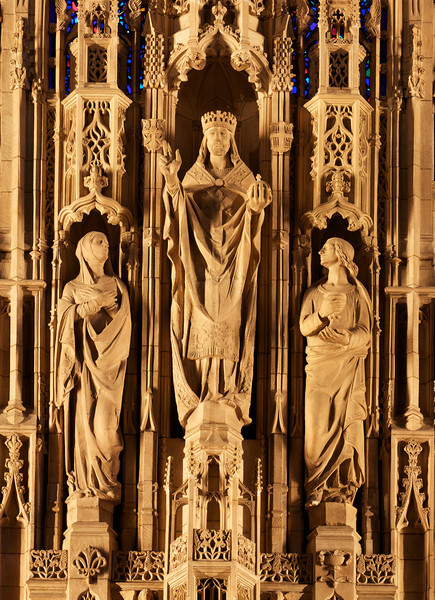 "Saint Thomas Church Reredos Statues of Christ the King (center), Blessed Virgin Mary (left), Saint John (right), Shaped by Lee Lawrie<br /> <br /> It is difficult to make out details of the spectacular Saint Thomas Church reredos, even from the closest pews. To provide more detail, I used a telephoto lens at 320 mm to capture the great detail of the statues. Christ the King is the center statue with the Blessed Virgin Mary on the left, and Saint John on the right.<br /> <br /> Bertram Grosvenor Goodhue was responsible for the theme and figures and won the American Institute of Architects' gold medal in 1925 for this effort. Sculptor Lee Lawrie shaped the figures' appearances, reflecting the individual personalities. Goodhue designed the church with Ralph Adams Cram. The carvings were executed in Boston from Dunville stone from Downsville, Wisconsin. When illuminated, the stone assumes the cast of ivory, according to ""A Walking Tour of Saint Thomas Church."""