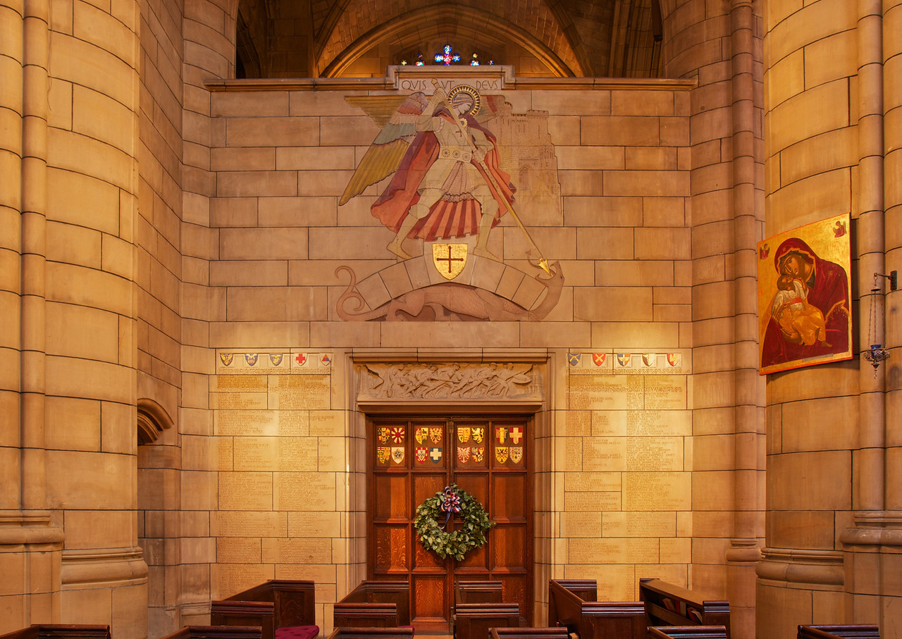 """Saint Thomas Church World War I Memorial by Lee Lawrie <br><br> At the top is the Archangel Michael, who drives his lance into the dragon. Below is relief of American soldiers going from America (represented by Saint Thomas Church) to France (represented by Rheims Catheral). The names on the wall are parishioners who served in the war. The names in gold at the top are those who gave their lives. The colored shields on the stone above the door are the branches of the armed services. On the door are the shields of the Allied Nations. Information from """"A Walking Tour of Saint Thomas Church."""" <br><br> Lee Lawrie (1877-1963) was one of the foremost architectural sculptors and a key figure in the American art scene preceding World War II, according to <a href=""""http://en.wikipedia.org/wiki/Lee_Lawrie """">Wikipedia. </a>  He produced over 300 commissions in styles ranging from Modern Gothic, Beaux-Arts Classicism and finally into Moderne or Art Deco. He worked on details on the Nebraska State Capitol building in Lincoln, Nebraska and some of the architectural sculpture and, his most prominent work, the free-standing bronze Atlas (installed 1937) at New York City's Rockefeller Center.  <br><br> Lawrie collaborated with architects Ralph Adams Cram and Bertram Goodhue that brought him widespread acclaim as one of the greatest architectural sculptors in America. Lawrie continued to work with Goodhue after the breakup of the Cram, Goodhue firm in 1914. After Goodhue's premature death in 1924, Lawrie continued to work with his successors. Lawrie's collaborations with Goodhue are arguably the most highly developed example of architectural sculpture in American architectural history according to Wikipedia. <br><br> After Goodhue's death, Lawrie went on to produce important and highly visible work under Raymond Hood at Rockefeller Center in New York City, which included the Atlas in collaboration with Rene Paul Chambellan. The statue is 45 feet tall with a 15-foot figure of Atlas supp"""
