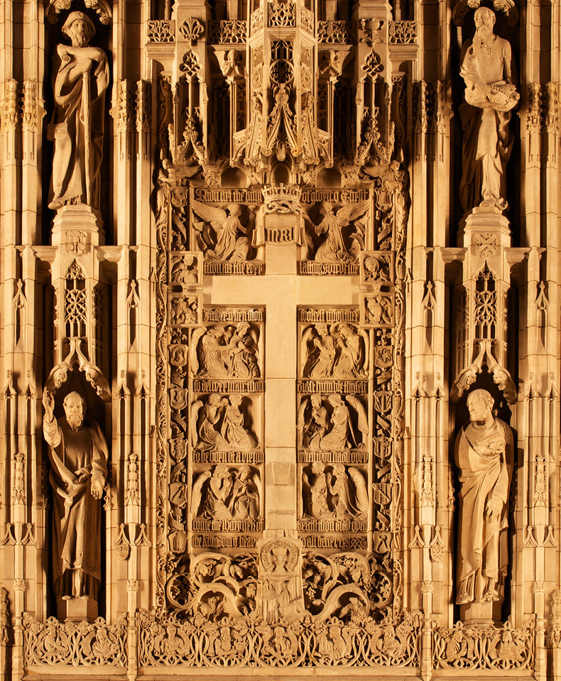 """Saint Thomas Reredos by Bertram Goodhue, Figures Shaped by Lee Lawrie<br /> <br /> Bertram Grosvenor Goodhue was responsible for the theme and figures and won the American Institute of Architects' gold medal in 1925 for this effort. Sculptor Lee Lawrie shaped the figures' appearances, reflecting the individual personalities. Goodhue designed the church with Ralph Adams Cram. The carvings were executed in Boston and depict the 12 Apostles, nine Hebrew prophets, Mary, John, and Christ, among others. The figure to the lower left hand corner is Saint Paul, Apostle to the Gentiles, lower right is Saint Peter, upper left, Saint James the Great, and upper right, Saint Andrew.<br /> <br /> The carvings are from Dunville stone from Downsville, Wisconsin. When illuminated, the stone assumes the cast of ivory, according to """"A Walking Tour of Saint Thomas Church."""""""