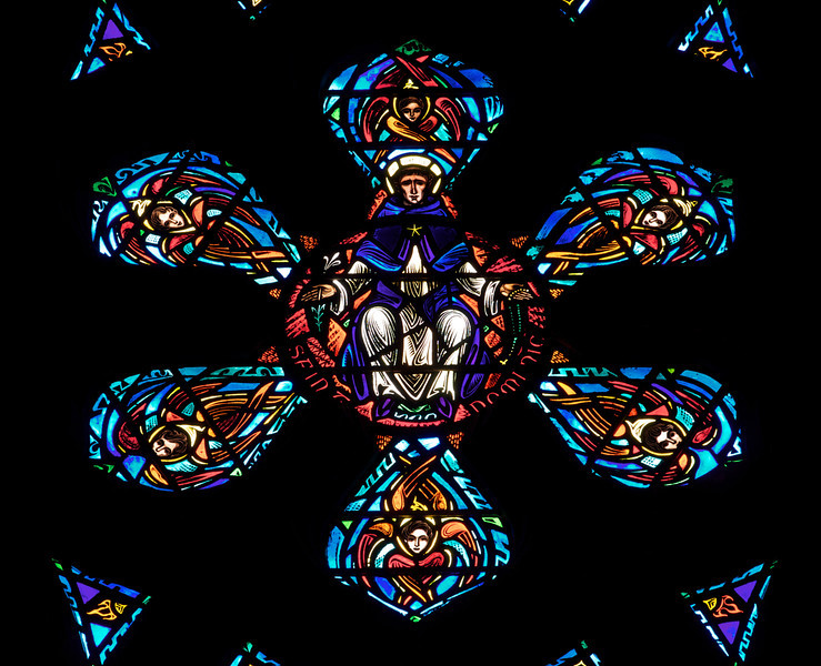 """Great Western Window of Saint Raymond of Penafort by Charles Connick <br><br> The Great Western Window at Saint Vincent Ferrer is beautiful, dominated by deep shades of blue. Charles Connick designed the window along with the other windows in the church. The lower center of the window is a depiction of Saint Dominic (1170-1221). According to <a href=""""http://en.wikipedia.org/wiki/Saint_Dominic """"> Wikipedia, </a> Saint Dominic was a Spanish priest and founder of the Dominican Order. Dominic is the patron saint of astronomers.  <br><br> From the  <a href=""""http://www.csvf.org/Architecture-M.html"""">church website: </a> <br><br> """"The dominant theme of the great Rose Window is """"the whole company of heaven, and all the powers therein,"""" marshaled under the nine choirs of angels. In medieval angelology, there were nine orders of angels: Angels, Archangels, Powers, Thrones, Dominations, Principalities, Virtues, Cherubim, and Seraphim. Orders are grouped around figures of saintly and celebrated Dominicans who serve as the representatives on earth of the distinctive spiritual qualities symbolized by the various members of the angelic choir. <br><br> The Great Western Window was made by the master craftsman Charles Connick, who worked under the direction of Bertram Goodhue, the architect of the church.   St. Dominic, surrounded by the Seraphim, whose name in Hebrew means 'the burning ones.' The Seraphim burn mostly brightly as those angels closest to God. A dream of his mother, Bl. Jane of Aza, foretold that Dominic would ignite the world on fire with his preaching."""" <br><br> Charles Connick (1875-1945) produced the spectacular stained glass windows in the church. Connick was a prominent artist best known for his work in stained glass in the Gothic Revival style. He was born in Crawford Country, Pennsylvania and developed an interest in drawing at an early age. He left high school when his father became disabled to become an illustrator on the staff of the Pittsburgh Press. At the"""
