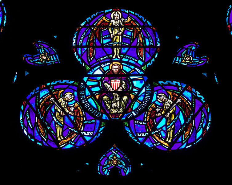 "Great Western Window of Saint Raymond of Penafort by Charles Connick <br><br> The Great Western Window at Saint Vincent Ferrer is beautiful, dominated by deep shades of blue and purple. Charles Connick designed the window along with the other windows in the church. The center of the window is a depiction of Saint Raymond of Penafort (1175-1275). According to <a href=""http://en.wikipedia.org/wiki/Raymond_of_Penyafort""> Wikipedia, </a> Raymond was a Catalan Dominican friar in the 13th-century, who compiled the Decretals of Gregory IX, a collection of canon laws that remained a major part of Church law until the 20th century. He is honored as a saint in the Catholic Church and is the patron saint of lawyers, especially canon lawyers. <br><br> He was educated in Barcelona and at the University of Bologna, where he received doctorates in both civil and canon law. From 1195 to 1210, he taught canon law. In 1210, he moved to Bologna, where he remained until 1222, including three years occupying the Chair of canon law at the university. He came to know the newly-founded Dominican Order there and entered it in 1216, at age 41.  <br><br> Raymond was instrumental in the founding of the Mercedarian friars in 1218. <br><br> Raymond died at the age of 100 in Barcelona in 1275 and was canonized by Pope Clement VIII in the year 1601. He was buried in Barcelona. <br><br> From the  <a href=""http://www.csvf.org/Architecture-M.html"">church website: </a> <br><br> ""The dominant theme of the great Rose Window is ""the whole company of heaven, and all the powers therein,"" marshaled under the nine choirs of angels. In medieval angelology, there were nine orders of angels: Angels, Archangels, Powers, Thrones, Dominations, Principalities, Virtues, Cherubim, and Seraphim. Orders are grouped around figures of saintly and celebrated Dominicans who serve as the representatives on earth of the distinctive spiritual qualities symbolized by the various members of the angelic choir. <br><br> The Great Western Window was made by the master craftsman Charles Connick, who worked under the direction of Bertram Goodhue, the architect of the church.  <br><br> St. Raymond of Penafort, the counsellor to the King of Aragon, surrounded by the Principalities, who are sent by God to protect earthly rulers."" <br><br> Charles Connick (1875-1945) produced the spectacular stained glass windows in the church. Connick was a prominent artist best known for his work in stained glass in the Gothic Revival style. He was born in Crawford Country, Pennsylvania and developed an interest in drawing at an early age. He left high school when his father became disabled to become an illustrator on the staff of the Pittsburgh Press. At the age of 19, he learned the art of stained glass as an apprentice in the shop of Rudy Brothers in Pittsburgh, where he stayed through 1899. He worked for a number of stained glass companies in Pittsburgh and New York. He went to England and France to study ancient and modern stained glass, including those in the Chartres Cathedral. His first major work was First Baptist Church in Pittsburgh in 1912.  <br><br> Connick settled in Boston opening a stained glass studio in Back Bay in 1913; the Charles J. Connick Associates Studio continued to operate after his death until 1986. He produced many notable windows in such churches as Saint Patrick's Cathedral, Saint John the Divine, the Princeton University Chapel, and Saint Vincent Ferrer. According to Wikipedia, the Charles J. Connick Associates Studio produced some 15,000 windows in more than 5,000 churches and public buildings. <br><br> According to <a href=""http://en.wikipedia.org/wiki/Charles_Connick"">Wikipedia, </a> ""Connick preferred to use clear ""antique"" glass, similar to that of the Middle Ages and praised this type of glass as ""colored radiance, with the lustre, intensity, and baffling vibrant quality of dancing lights."" He employed a technique of ""staggered"" solder-joints in his leading and bars, which English stained-glass historian Peter Cormack says gives the windows their ""syncopated or 'swinging' character."" His style incorporated a strong interest in symbolism as well. Connick expressed the opinion that stained glass's first job was to serve the architectural effect and he believed that his greatest contribution to glasswork was ""rescuing it from the abysmal depth of opalescent picture windows"" of the sort popularized by Louis Comfort Tiffany and John La Farge. Although firmly committed to a regenerated handicraft tradition, Connick welcomed innovation and experimentation in design and technique among his co-workers at his studio."" <br><br> According to the <a href=""http://www.cjconnick.org/"">Charles J. Connick Stained Glass Foundation website</a> ""Using pure, intense color and strong linear design, this guild of artists led the modern revitalization of medieval stained glass craftsmanship in the United States.  Their work reflected a strong interest in symbolism in design and color, and stressed the importance of the relationship between the window's design and its surrounding architecture.  As if with one mind and one pair of hands, the craftsmen in the Connick Studio worked collectively on their windows like the 12th- and 13th- century artisans whose craft inspired them."" <br><br> The Charles J. Connick Stained Glass Foundation was formed after the studio closed in 1986. According to the <a href=""http://www.cjconnick.org/"">foundation website</a> ""The mission of the Charles J. Connick Stained Glass Foundation, Ltd. is to promote the true understanding of the glorious medium of color and light and to preserve and perpetuate the Connick tradition of stained glass."" <br><br> Here is an interesting <a href=""http://video.mit.edu/watch/charles-j-connick-and-mit-10153/"">video from the Massachusetts Institute of Technology</a> on Connick. In December 2008, the foundation donated materials to MIT's Rotch Library of Architecture and Planning to form the Charles J. Connick Stained Glass Foundation Collection."