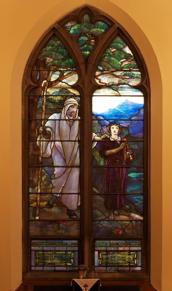 "The Second Reformed Church The Good Shepherd Window <br><br> From <a href=""http://www.secondreformed.org/stainedglass"">the church website:</a> <br><br> ""Please look carefully at the grain in the wooden staff, the bark of the tree, the rich colors in the folds of the garments, as well as the thickness variations of the drapery  glass. Remember every piece of glass was planned for and created to be used in that specific place in this particular window. There is no lead separating the sky and mountain. This helps the mountain recede into the distance."" <br><br> Louis Comfort Tiffany (1848-1933) was one of America's most acclaimed artists and is most associated with the Art Nouveau and Aesthetic movements according to <a href=""http://en.wikipedia.org/wiki/Louis_Comfort_Tiffany"">Wikipedia.</a> He focused in the decorative arts and is best known for his work in stained glass. He was the son of Charles Lewis Tiffany (1812-1902), founder of Tiffany & Company. Lewis chose to pursue his own artistic interests rather than joining the family business.  <br><br> He began his career as a painter and traveled extensively through Europe. In the late 1870s, Tiffany turned his attention to decorative arts and interiors. In 1881, he did the interior design of the Mark Twain House in Hartford Connecticut. His most notable work was in 1862 when President Chester Arthur refused to move into the White House until it had been resorted, according to Wikipedia. He commissioned Tiffany, who had begun to make a name for himself for interior design work, to redo the state rooms. Tiffany worked on the East Room, Blue Room, Red Room, the State Dining Room, and the Entrance Hall.  <br><br> From  <a href=""http://www.metmuseum.org/toah/hd/tiff/hd_tiff.htm"">The Metropolitan Museum website:</a> ""By late 1892 or early 1893, Tiffany built a glasshouse in Corona, Queens, New York, and, with Arthur Nash, a skilled glassworker from Stourbridge, England, his furnaces developed a method whereby different colors were blended together in the molten state, achieving subtle effects of shading and texture. Recalling the Old English word fabrile (hand-wrought), Tiffany named the blown glass from his furnaces Favrile, a trademark that signified glass of hand-made and unique quality."" <br><br> ""Of all of Tiffany's artistic endeavors, leaded-glass brought him the greatest recognition. Tiffany and his early rival, John La Farge, revolutionized the look of stained glass, which had remained essentially unchanged since medieval times when craftsmen utilized flat panes of white and colored glass with details painted with glass paints before firing and leading. Tiffany and La Farge experimented with new types of glass and achieved a more varied palette with richer hues and greater density. By 1881, each had patented an opalescent glass, a unique American phenomenon that featured a milky, opaque, and sometimes rainbow-hued appearance with the introduction of light. Internally colored with variegated shades of the same or different hues, Tiffany's Favrile glass enabled craftsmen to substitute random tonal gradations, lines, textures, and densities inherent in the material itself for pictorial details."" <br><br> At its peak, his factory employed over 300 artisans. He was appointed as art director at Tiffany & Company upon his father's death in 1902. <br><br> Tiffany lived during the Gilded Age, a period of rapid church expansion; one source reports that there were 4,000 churches under contraction in the U.S. in the 1880s according to a recent <a href=""http://www.nytimes.com/2013/01/01/arts/design/louis-c-tiffany-works-at-museum-of-biblical-art.html?ref=louiscomforttiffany"">The New York Times article</a> on an exhibit of Tiffany's ecclesiastical work. There was a great demand for artists that could create great and inspiring stained glass windows, mosaics, rederos, and altars. Many churches turned to Tiffany to create such beautiful works. His work in New York churches include Saint Michaels, Advent Lutheran, Saint Ignatius Loyola, Temple Emmanu-El, Church of the Incarnation, Holy Trinity Lutheran Church, Eldridge Street Synagogue; in New Jersey, numerous windows are in Second Reformed Church of Hackensack. <br><br> After fire destroyed their first church, The Second Reform Church in Hackensack, New Jersey contacted Tiffany requesting windows depicting events in the life of Christ and contracted Tiffany Studios for five windows, according to <a href=""http://www.secondreformed.org/clientimages/42874/stainedglasswindows/stained%20glass%20window%20info.pdf"">the church website.</a> The church also contracted Duffner & Kimberly Co. for one window.  The installation of these windows was competed before the dedication ceremony in 1909.  <br><br> From the church website: <br><br> ""The New York Times (May 4, 1979) wrote: ""Some of Tiffany's favorite windows are in the Second Reformed Church in Hackensack ,... Tiffany frequently visited there with clients in tow, using  the visit to help them select appropriate design for their purposes."" For each installation, the design was customized as the client requested and reworked to fit the window's opening size and shape requirements. Colors were coordinated to harmonize with the surroundings in each location."""