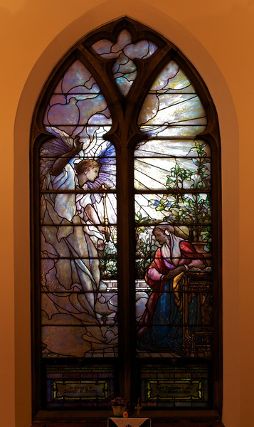 "The Second Reformed Church Christ, The Annunciation Window <br><br> From <a href="" http://www.secondreformed.org/stainedglass"">the church website</a> <br><br> ""Notice how all the lines radiate from the Angel. This Angel has appeared to tell Mary that she is with Child. Look at the beautiful classical drapery of the Angel's robes. The glass is full of color in the folds. Lead lines follow the contours. There are lilies surrounding Mary. Note how the Angel's glowing form sheds light over Mary and illuminates her upper body."" <br><br> Louis Comfort Tiffany (1848-1933) was one of America's most acclaimed artists and is most associated with the Art Nouveau and Aesthetic movements according to <a href=""http://en.wikipedia.org/wiki/Louis_Comfort_Tiffany"">Wikipedia.</a> He focused in the decorative arts and is best known for his work in stained glass. He was the son of Charles Lewis Tiffany (1812-1902), founder of Tiffany & Company. Lewis chose to pursue his own artistic interests rather than joining the family business.  <br><br> He began his career as a painter and traveled extensively through Europe. In the late 1870s, Tiffany turned his attention to decorative arts and interiors. In 1881, he did the interior design of the Mark Twain House in Hartford Connecticut. His most notable work was in 1862 when President Chester Arthur refused to move into the White House until it had been resorted, according to Wikipedia. He commissioned Tiffany, who had begun to make a name for himself for interior design work, to redo the state rooms. Tiffany worked on the East Room, Blue Room, Red Room, the State Dining Room, and the Entrance Hall.  <br><br> From  <a href=""http://www.metmuseum.org/toah/hd/tiff/hd_tiff.htm"">The Metropolitan Museum website:</a> ""By late 1892 or early 1893, Tiffany built a glasshouse in Corona, Queens, New York, and, with Arthur Nash, a skilled glassworker from Stourbridge, England, his furnaces developed a method whereby different colors were blended together in the molten state, achieving subtle effects of shading and texture. Recalling the Old English word fabrile (hand-wrought), Tiffany named the blown glass from his furnaces Favrile, a trademark that signified glass of hand-made and unique quality."" <br><br> ""Of all of Tiffany's artistic endeavors, leaded-glass brought him the greatest recognition. Tiffany and his early rival, John La Farge, revolutionized the look of stained glass, which had remained essentially unchanged since medieval times when craftsmen utilized flat panes of white and colored glass with details painted with glass paints before firing and leading. Tiffany and La Farge experimented with new types of glass and achieved a more varied palette with richer hues and greater density. By 1881, each had patented an opalescent glass, a unique American phenomenon that featured a milky, opaque, and sometimes rainbow-hued appearance with the introduction of light. Internally colored with variegated shades of the same or different hues, Tiffany's Favrile glass enabled craftsmen to substitute random tonal gradations, lines, textures, and densities inherent in the material itself for pictorial details."" <br><br> At its peak, his factory employed over 300 artisans. He was appointed as art director at Tiffany & Company upon his father's death in 1902. <br><br> Tiffany lived during the Gilded Age, a period of rapid church expansion; one source reports that there were 4,000 churches under contraction in the U.S. in the 1880s according to a recent <a href=""http://www.nytimes.com/2013/01/01/arts/design/louis-c-tiffany-works-at-museum-of-biblical-art.html?ref=louiscomforttiffany"">The New York Times article</a> on an exhibit of Tiffany's ecclesiastical work. There was a great demand for artists that could create great and inspiring stained glass windows, mosaics, rederos, and altars. Many churches turned to Tiffany to create such beautiful works. His work in New York churches include Saint Michaels, Advent Lutheran, Saint Ignatius Loyola, Temple Emmanu-El, Church of the Incarnation, Holy Trinity Lutheran Church, Eldridge Street Synagogue; in New Jersey, numerous windows are in Second Reformed Church of Hackensack. <br><br> After fire destroyed their first church, The Second Reform Church in Hackensack, New Jersey contacted Tiffany requesting windows depicting events in the life of Christ and contracted Tiffany Studios for five windows, according to <a href=""http://www.secondreformed.org/clientimages/42874/stainedglasswindows/stained%20glass%20window%20info.pdf"">the church website.</a> The church also contracted Duffner & Kimberly Co. for one window.  The installation of these windows was competed before the dedication ceremony in 1909.  <br><br> From the church website: <br><br> ""The New York Times (May 4, 1979) wrote: ""Some of Tiffany's favorite windows are in the Second Reformed Church in Hackensack ,... Tiffany frequently visited there with clients in tow, using  the visit to help them select appropriate design for their purposes."" For each installation, the design was customized as the client requested and reworked to fit the window's opening size and shape requirements. Colors were coordinated to harmonize with the surroundings in each location."""
