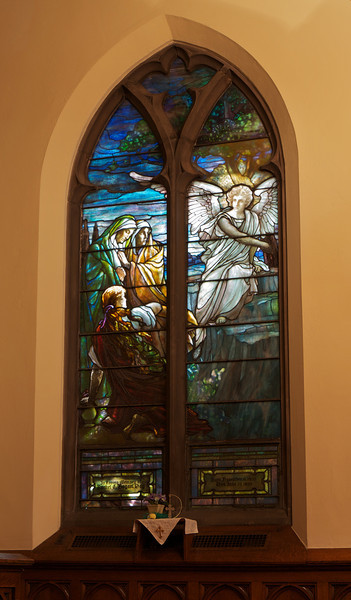 "The Second Reformed Church Christ, The Three Marys at the Tomb Window <br><br> From <a href=""http://www.secondreformed.org/stainedglass"">the church website:</a> <br><br> ""Observe how the angel radiates light that illuminates the scene. The artist captures effect of the light on the hair of the women. Artists strive to achieve this look on canvas with a brush and a variety of paints. Here there has been no application of paint.  The streaks of color within the glass give the appearance of strands of hair.  This utilization of Tiffany glass is particularly beautiful  on the kneeling women. Note the plated glass effects. Plating is a method of building layers to modulate the light coming through to achieve special effects and colors. A large piece of glass was layered over the top of leaded pieces that make up part of the rocks. Used here, the plating helps to diminish the importance of the rocks in the design.  The viewer instead focuses on the figures. A metal bar was designed to conform to the head of the angel, thus providing the necessary structural support and enhancing the overall design. Imagine how a straight support bar crossing the angel's head would have interfered with the beauty of this work."" <br><br> Louis Comfort Tiffany (1848-1933) was one of America's most acclaimed artists and is most associated with the Art Nouveau and Aesthetic movements according to <a href=""http://en.wikipedia.org/wiki/Louis_Comfort_Tiffany"">Wikipedia.</a> He focused in the decorative arts and is best known for his work in stained glass. He was the son of Charles Lewis Tiffany (1812-1902), founder of Tiffany & Company. Lewis chose to pursue his own artistic interests rather than joining the family business.  <br><br> He began his career as a painter and traveled extensively through Europe. In the late 1870s, Tiffany turned his attention to decorative arts and interiors. In 1881, he did the interior design of the Mark Twain House in Hartford Connecticut. His most notable work was in 1862 when President Chester Arthur refused to move into the White House until it had been resorted, according to Wikipedia. He commissioned Tiffany, who had begun to make a name for himself for interior design work, to redo the state rooms. Tiffany worked on the East Room, Blue Room, Red Room, the State Dining Room, and the Entrance Hall.  <br><br> From  <a href=""http://www.metmuseum.org/toah/hd/tiff/hd_tiff.htm"">The Metropolitan Museum website:</a> ""By late 1892 or early 1893, Tiffany built a glasshouse in Corona, Queens, New York, and, with Arthur Nash, a skilled glassworker from Stourbridge, England, his furnaces developed a method whereby different colors were blended together in the molten state, achieving subtle effects of shading and texture. Recalling the Old English word fabrile (hand-wrought), Tiffany named the blown glass from his furnaces Favrile, a trademark that signified glass of hand-made and unique quality."" <br><br> ""Of all of Tiffany's artistic endeavors, leaded-glass brought him the greatest recognition. Tiffany and his early rival, John La Farge, revolutionized the look of stained glass, which had remained essentially unchanged since medieval times when craftsmen utilized flat panes of white and colored glass with details painted with glass paints before firing and leading. Tiffany and La Farge experimented with new types of glass and achieved a more varied palette with richer hues and greater density. By 1881, each had patented an opalescent glass, a unique American phenomenon that featured a milky, opaque, and sometimes rainbow-hued appearance with the introduction of light. Internally colored with variegated shades of the same or different hues, Tiffany's Favrile glass enabled craftsmen to substitute random tonal gradations, lines, textures, and densities inherent in the material itself for pictorial details."" <br><br> At its peak, his factory employed over 300 artisans. He was appointed as art director at Tiffany & Company upon his father's death in 1902. <br><br> Tiffany lived during the Gilded Age, a period of rapid church expansion; one source reports that there were 4,000 churches under contraction in the U.S. in the 1880s according to a recent <a href=""http://www.nytimes.com/2013/01/01/arts/design/louis-c-tiffany-works-at-museum-of-biblical-art.html?ref=louiscomforttiffany"">The New York Times article</a> on an exhibit of Tiffany's ecclesiastical work. There was a great demand for artists that could create great and inspiring stained glass windows, mosaics, rederos, and altars. Many churches turned to Tiffany to create such beautiful works. His work in New York churches include Saint Michaels, Advent Lutheran, Saint Ignatius Loyola, Temple Emmanu-El, Church of the Incarnation, Holy Trinity Lutheran Church, Eldridge Street Synagogue; in New Jersey, numerous windows are in Second Reformed Church of Hackensack. <br><br> After fire destroyed their first church, The Second Reform Church in Hackensack, New Jersey contacted Tiffany requesting windows depicting events in the life of Christ and contracted Tiffany Studios for five windows, according to <a href=""http://www.secondreformed.org/clientimages/42874/stainedglasswindows/stained%20glass%20window%20info.pdf"">the church website.</a> The church also contracted Duffner & Kimberly Co. for one window.  The installation of these windows was competed before the dedication ceremony in 1909.  <br><br> From the church website: <br><br> ""The New York Times (May 4, 1979) wrote: ""Some of Tiffany's favorite windows are in the Second Reformed Church in Hackensack ,... Tiffany frequently visited there with clients in tow, using  the visit to help them select appropriate design for their purposes."" For each installation, the design was customized as the client requested and reworked to fit the window's opening size and shape requirements. Colors were coordinated to harmonize with the surroundings in each location."""