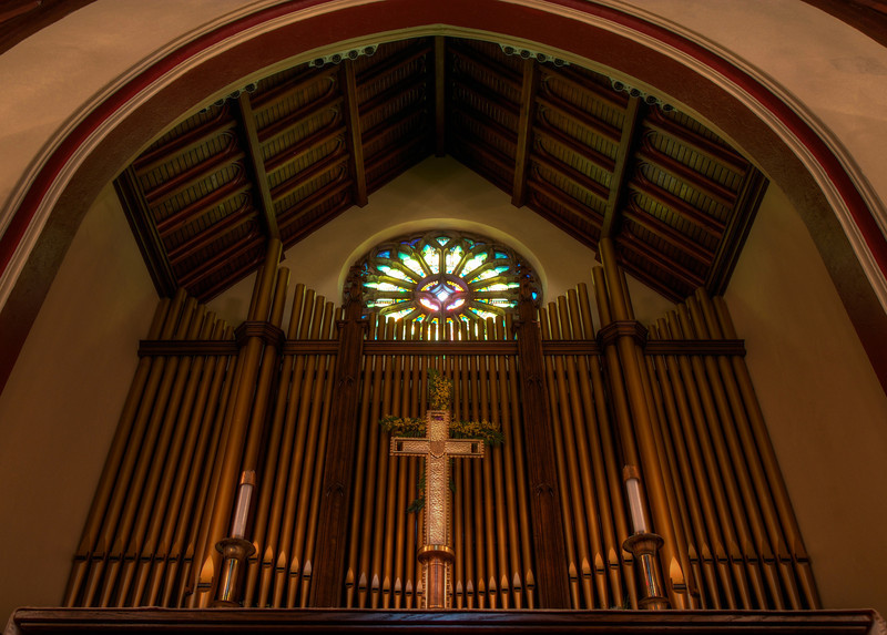 """The Second Reformed Church Rose Window <br><br> From <a href=""""http://www.secondreformed.org/stainedglass"""">the church website</a> <br><br> """"When our current building was built, Tiffany was commissioned to create this beautiful window which is very interactive during morning worship. Sometimes the deep olive green predominates. Some days a beautiful blue is seen at the outer edge. Other days when the sunlight strikes it directly, it is golden and so radiant that the star in the center is not able to be seen. <br><br> The Metropolitan Museum of Art noted at the time of the installation in 1909, """"...under the personal supervision of Mr. Louis C. Tiffany, has been placed in the Church-'a magnificent Rose Window containing a jeweled cross, extending through many openings in the circle with an illuminated background representing the sky'""""."""" <br><br> Below the window is the 38 rank Austin pipe organ, installed in 1978.  <br><br> Louis Comfort Tiffany (1848-1933) was one of America's most acclaimed artists and is most associated with the Art Nouveau and Aesthetic movements according to <a href=""""http://en.wikipedia.org/wiki/Louis_Comfort_Tiffany"""">Wikipedia.</a> He focused in the decorative arts and is best known for his work in stained glass. He was the son of Charles Lewis Tiffany (1812-1902), founder of Tiffany & Company. Lewis chose to pursue his own artistic interests rather than joining the family business.  <br><br> He began his career as a painter and traveled extensively through Europe. In the late 1870s, Tiffany turned his attention to decorative arts and interiors. In 1881, he did the interior design of the Mark Twain House in Hartford Connecticut. His most notable work was in 1862 when President Chester Arthur refused to move into the White House until it had been resorted, according to Wikipedia. He commissioned Tiffany, who had begun to make a name for himself for interior design work, to redo the state rooms. Tiffany worked on the East Room, Blue Room, Red Room,"""