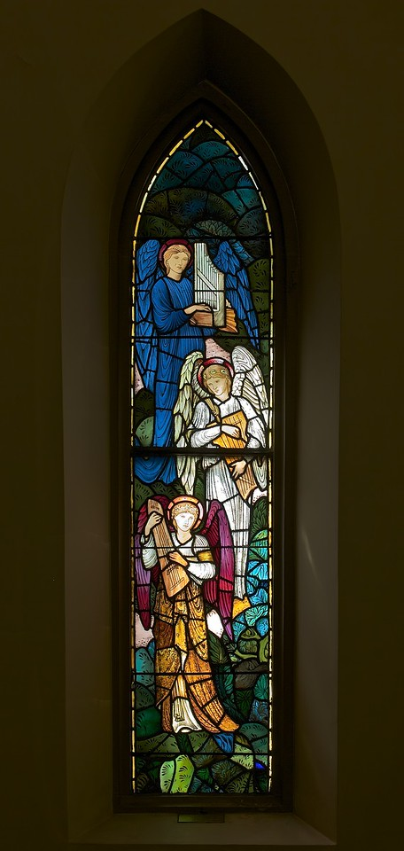 "The Church of the Incarnation, Infant Children by William Morris <br><br> <a href=""http://www.churchoftheincarnation.org/about-incarnation/landmark-building/the-window-tour/infant-children-7/"">Incarnation website:</a> ""This pair of angel windows was given in memory of all infant children. Their design is strikingly modern. The individual pieces of stained glass have no shadings. Instead, the artist assembled flat planes of vivid colored glass for a collage effect. The outlines of the figures and other details are painted in simple black lines. They were executed by the William Morris Company of London, a leader in the English Arts and Crafts movement. Morris is considered by many as the ""father of graphic design."""" <br><br> Morris (1834-1896) was an English textile designer, artist, writer, socialist associated with the Pre-Raphaelite Brotherhood and English Arts and Crafts Movement. ""He founded a design firm in partnership with the artist Edward Burne-Jones, and the poet and artist Dante Gabriel Rossetti which profoundly influenced the decoration of churches and houses into the early 20th century. As an author, illustrator and medievalist, he helped to establish the modern fantasy genre, and was a direct influence on postwar authors such as J. R. R. Tolkien. He was also a major contributor to reviving traditional textile arts and methods of production, and one of the founders of the Society for the Protection of Ancient Buildings, now a statutory element in the preservation of historic buildings in the UK. <br><br> Morris wrote and published poetry, fiction, and translations of ancient and medieval texts throughout his life. His best-known works include The Defence of Guenevere and Other Poems (1858), The Earthly Paradise (1868–1870), A Dream of John Ball (1888), the utopian News from Nowhere (1890), and the fantasy romance The Well at the World's End (1896). He was an important figure in the emergence of socialism in Britain, founding the Socialist League in 1884, but breaking with that organization over goals and methods by the end of the decade. He devoted much of the rest of his life to the Kelmscott Press, which he founded in 1891. Kelmscott was devoted to the publishing of limited-edition, illuminated-style print books. The 1896 Kelmscott edition of the Works of Geoffrey Chaucer is considered a masterpiece of book design,"" according to <a href=""http://en.wikipedia.org/wiki/William_Morris"">Wikipedia.</a>"