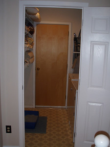 Laundry room - wood door at the back is utility closet (heat & hot water). Master bedroom is on the other side of the left wall, next condo over is on the other side of the right.  Shelving on the left side, door you can close to shut the area and sound away - this room is a very nice feature.