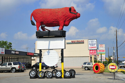 This big red bull (no horns) used to advertise a Mexican beer joint.  Today it serves as a prop for one of many Long Point tire shops.  It is near Long Point and Bingle.