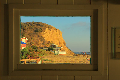502 - This image uses the window in the exhibition room as the frame for the bluff and cabin at the south end of the Rocky Bight beach.  I shot it at a slight angle and had to adjust/distort it to line the window edge to the image border.