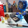 """My latest setup has changed somewhat. I've replaced the Hakko soldering iron with a newer Hakko model FX-601. On the right is a Edsyn """"Fuminator, on the left is automatic transmission oil and in the center is a Hakko 599B soldering tip cleaner. The Hakko 599B can be used instead of the sponge, but I still prefer using the wet sponge. The Inland 100W soldering iron is also shown with Stay Clean acid flux."""