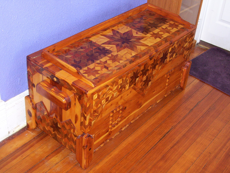 "Front, Side and Top 2007<br /> In 1980 I made a Cedar chest for my daughter, for a ""hope chest"". She was to use half of her allowance to buy things to fill it for when she got married. I framed it out of Cedar, and then overlaid it using diamonds and triangles cut from Cedar, Walnut and Hedge (Osage Orange or Bois D'Arc). The Hedge was from an old Hedge post I had on the place here. Hedge starts out nice and yellow as you can see on the 1980 picture, but darkens up darker than Walnut as you can see in the later pictures. I made the handles and everything out of wood. (I'm cheep that way) I had to kind of feel my way along as I made it. I used 2 or 3 methods in gluing the pieces on and finally settled on one I've been using ever since. They all seemed to work as no pieces have ever come off. Debbie still has it at the foot of her bed."