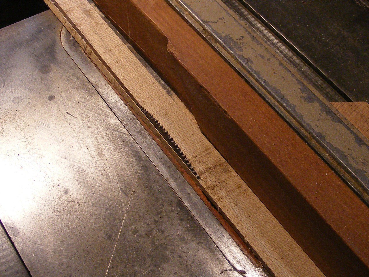 3 - Making a Tumbling Block Cribbage Board <br /> This picture shows the strip as it is part way through the cut. I use a hollow ground plywood blade in trimming the strips and in cutting the pieces. The blade will make a satin smooth cut. When the blade needs sharpening, I do that then in putting it back on the spindle I tighten the nut and spin the blade by hand a few turns. You will see the blade has a little wobble. I loosen the nut and turn the blade a bit on the spindle and then tighten the nut. I do this until I find the place where the wobble is taken out. It doesn't take much of a wobble to be over .005.