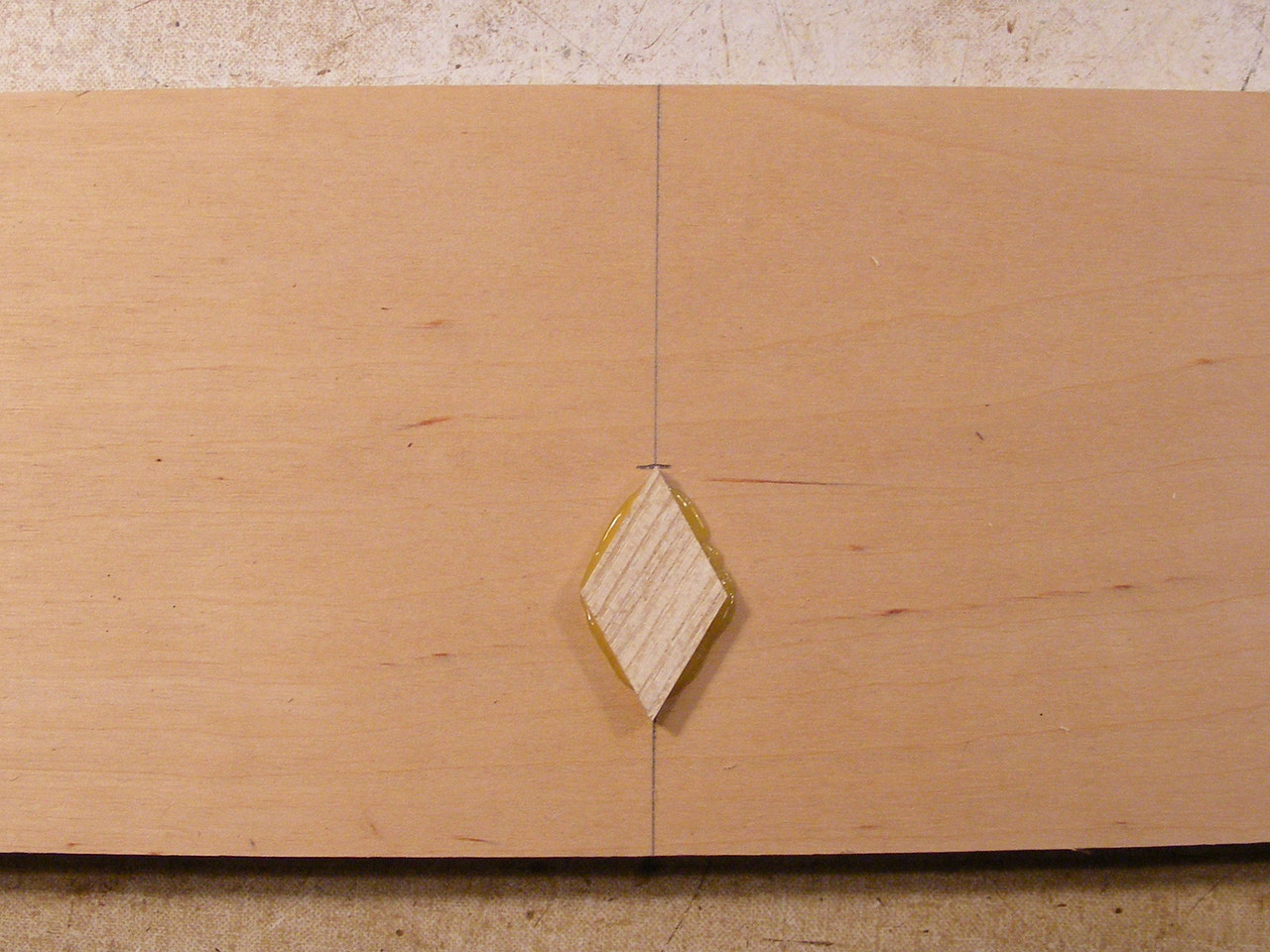 "7 - Making a Tumbling Block Cribbage Board  I take a blank piece of Baltic Birch plywood, 5/8th to ¾"" thick and mark the center. As you look at this diamond that I have glued on, you will see that the grain of the wood goes up and out of the diamond at the top right and the bottom left. It will be the same on each diamond that I glue on the Cribbage Board. If you turn it so that the point is up, on each type of wood, the grain will go out of the diamond to the right, at the top. To me this is more uniform and more pleasing to the eye when the whole thing is done.  I use hot glue to glue the diamonds and triangles on to the base. I use ""Super Amber"" Hot glue sticks from Supergrit (or Red Hill Corporation) at;  <a href=""http://www.supergrit.com/products/products_glue-hotmelt.asp"" rel=""nofollow"">www.supergrit.com/products/products_glue-hotmelt.asp</a>    The glue that squishes out I trim off with a chisel if it cools and hardens up before I can put another diamond in next to it."
