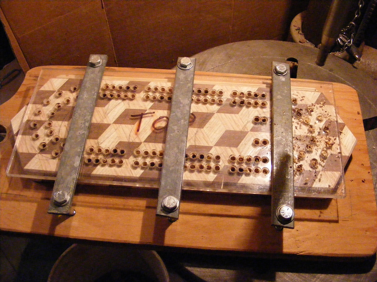 "27 - Making a Tumbling Block Cribbage Board <br /> I took a piece of ¼"" clear plastic and marked and drilled the holes then countersunk the edges of each hole a little. I use a self-centering bit to get the holes where I want them. I place the plastic where I want it and hold it in place with the 3 hold-down straps. I leave 2 straps holding the plastic when I am drilling the holes under the one I move aside. With the self-centering bit, you need to clean out the holes after you take the plastic off but you have them uniform at least."